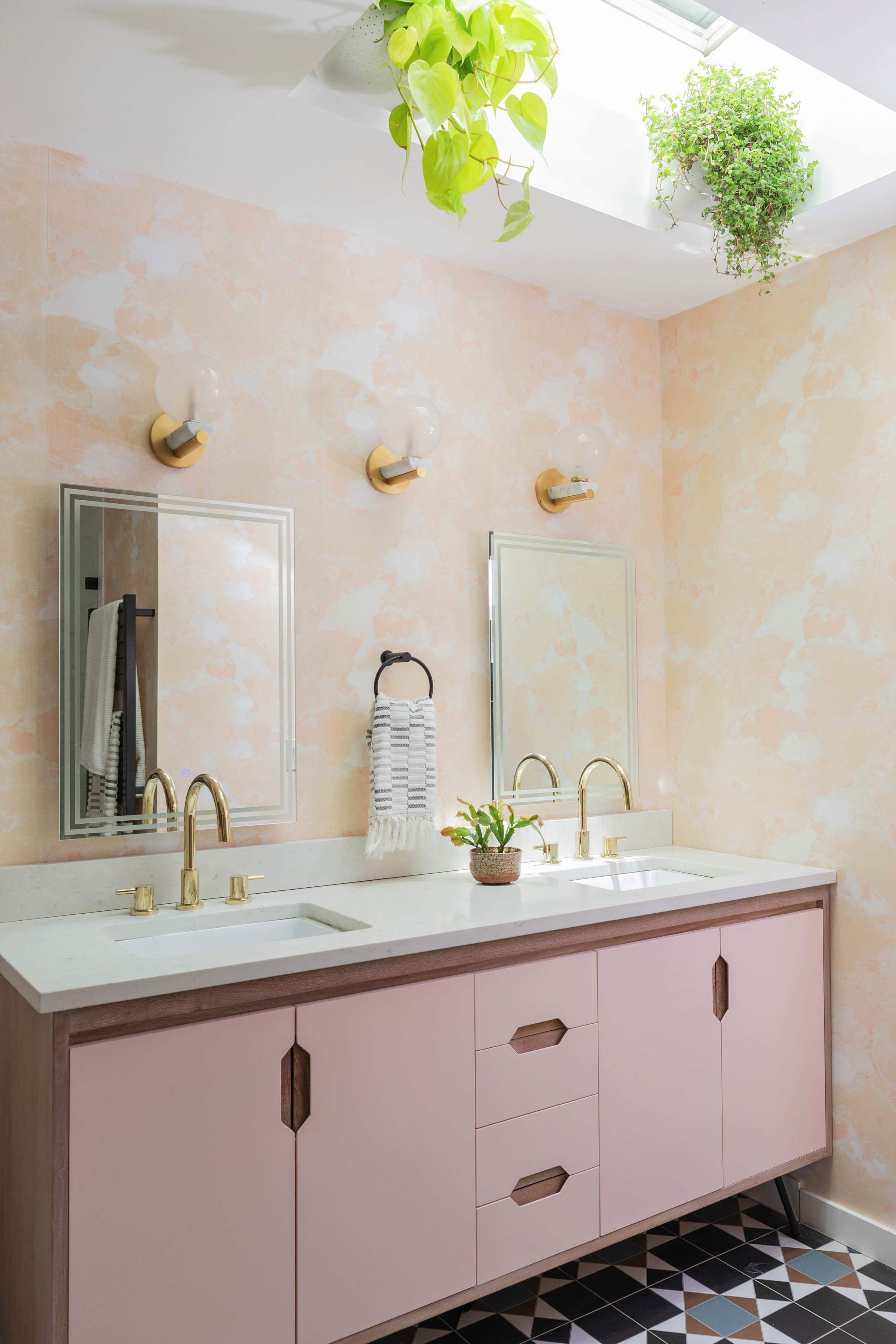 A blush colored bathroom with pink double vanity and a skylight that has plants hanging from it.