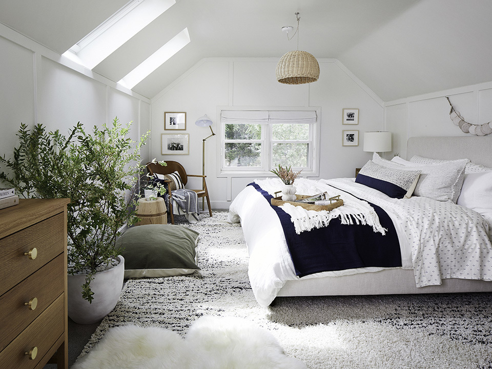 A bedroom with two skylights and blue and white decor.