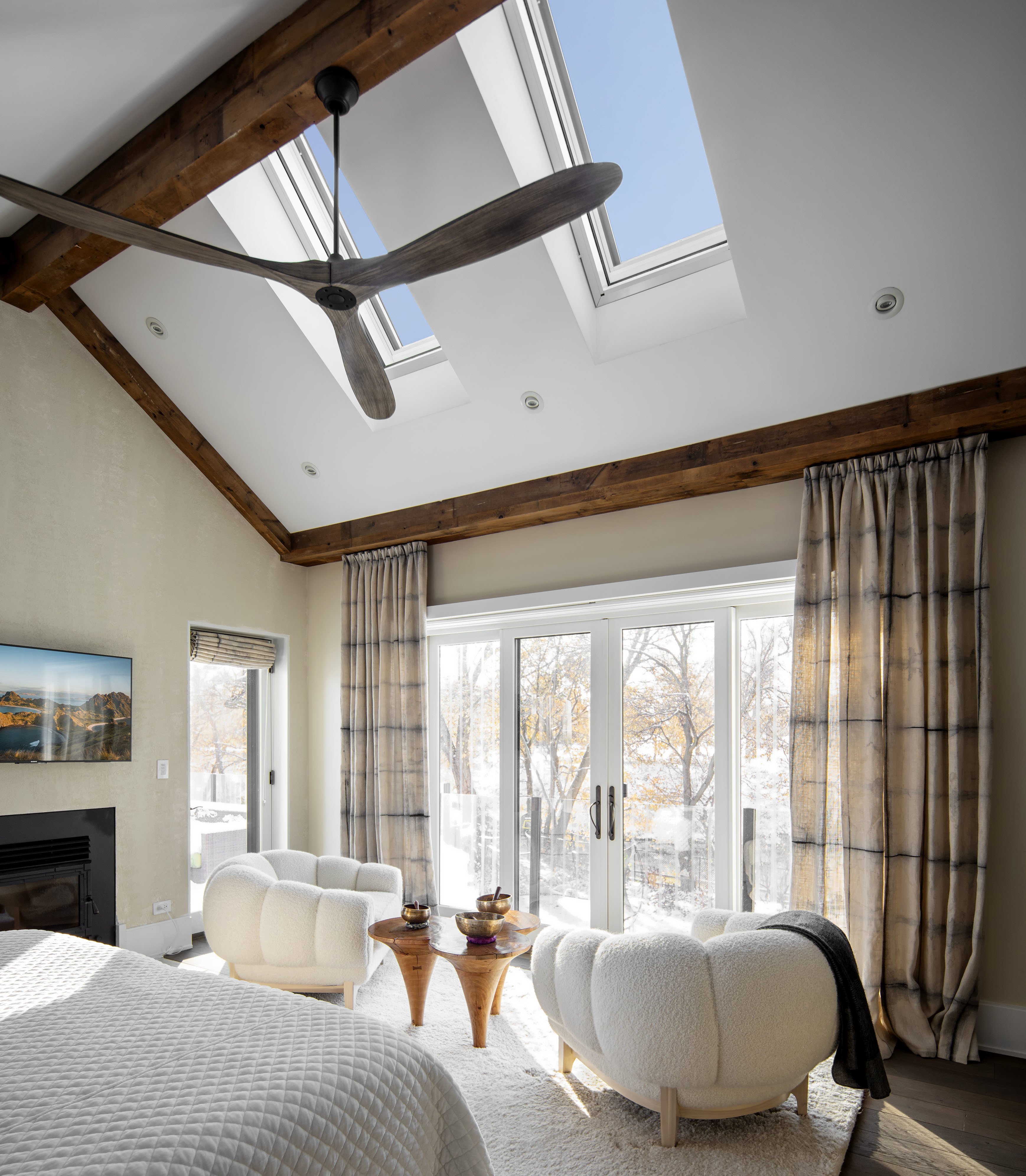 Neutral color master bedroom skylights exposed wooden beams
