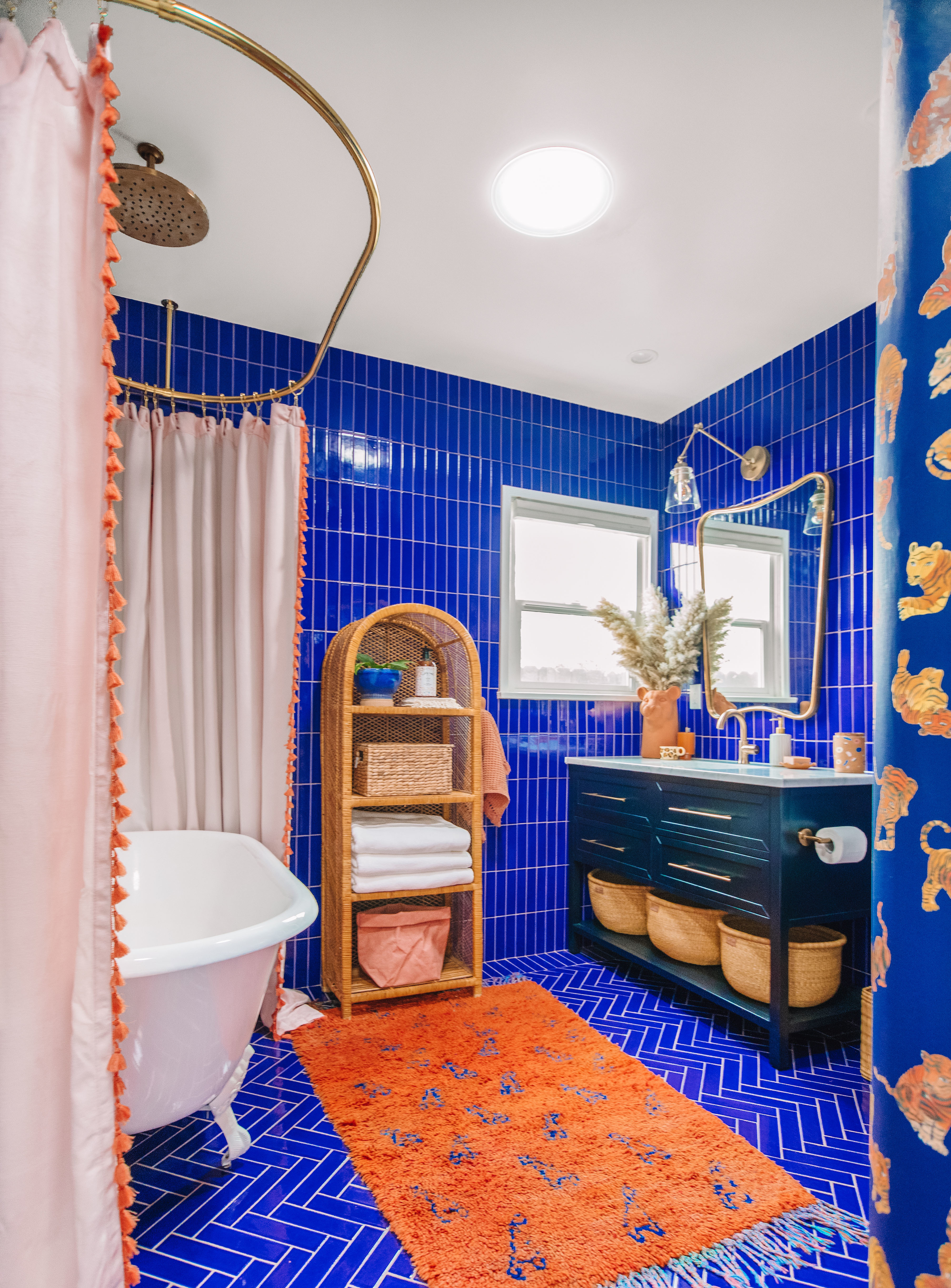 Bathroom with royal blue tile and terra cotta accents with claw foot bathtub