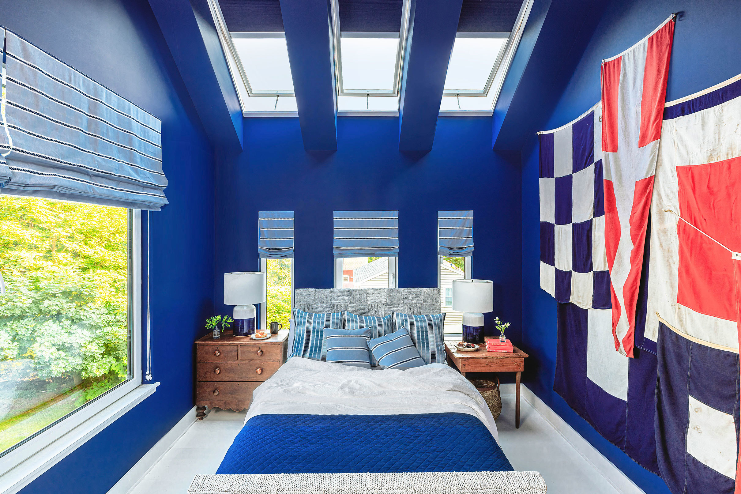 A bedroom painted royal blue with three skylights that have matching blue shades