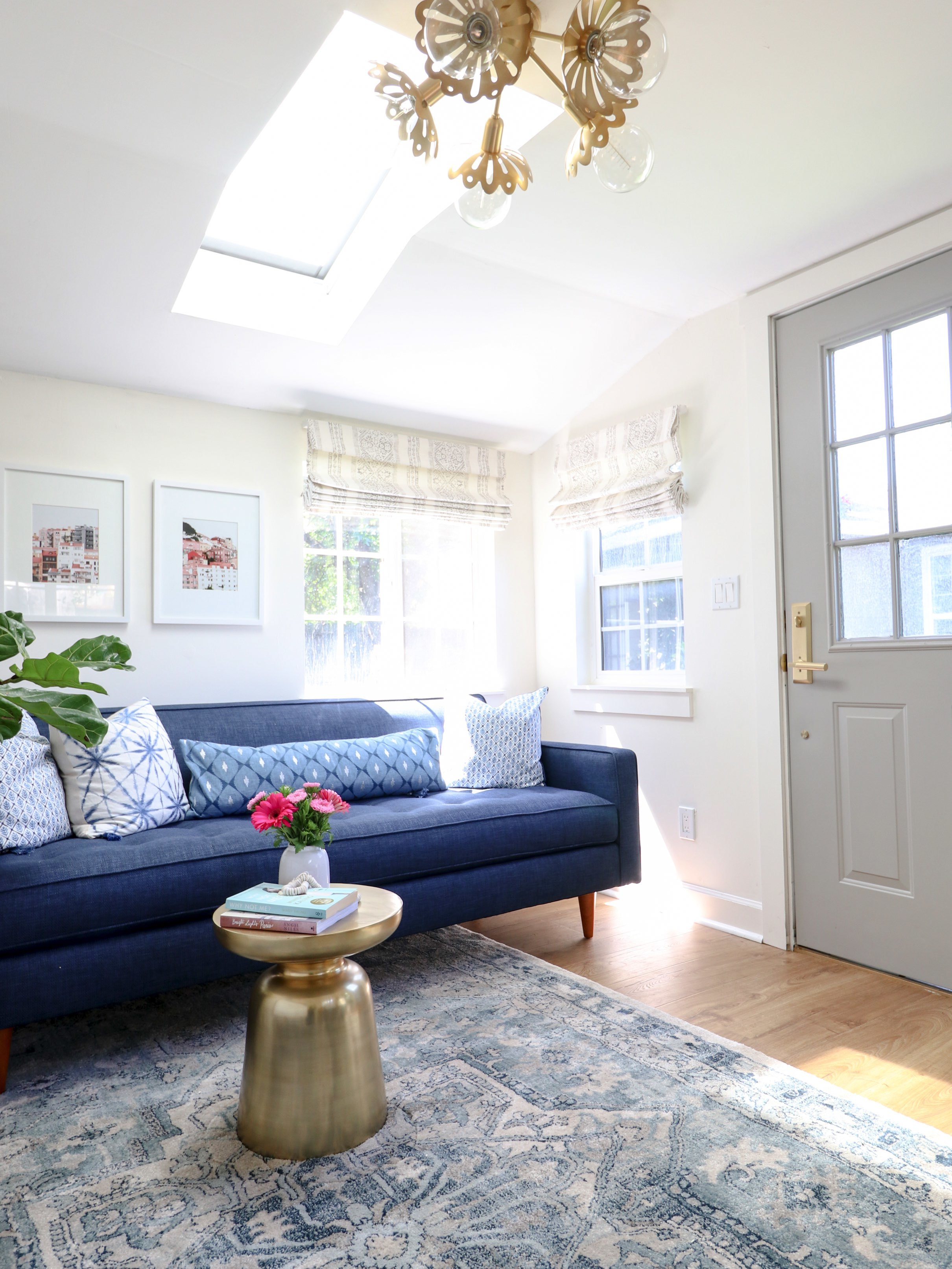 Blue sofa under a skylight brass pendant