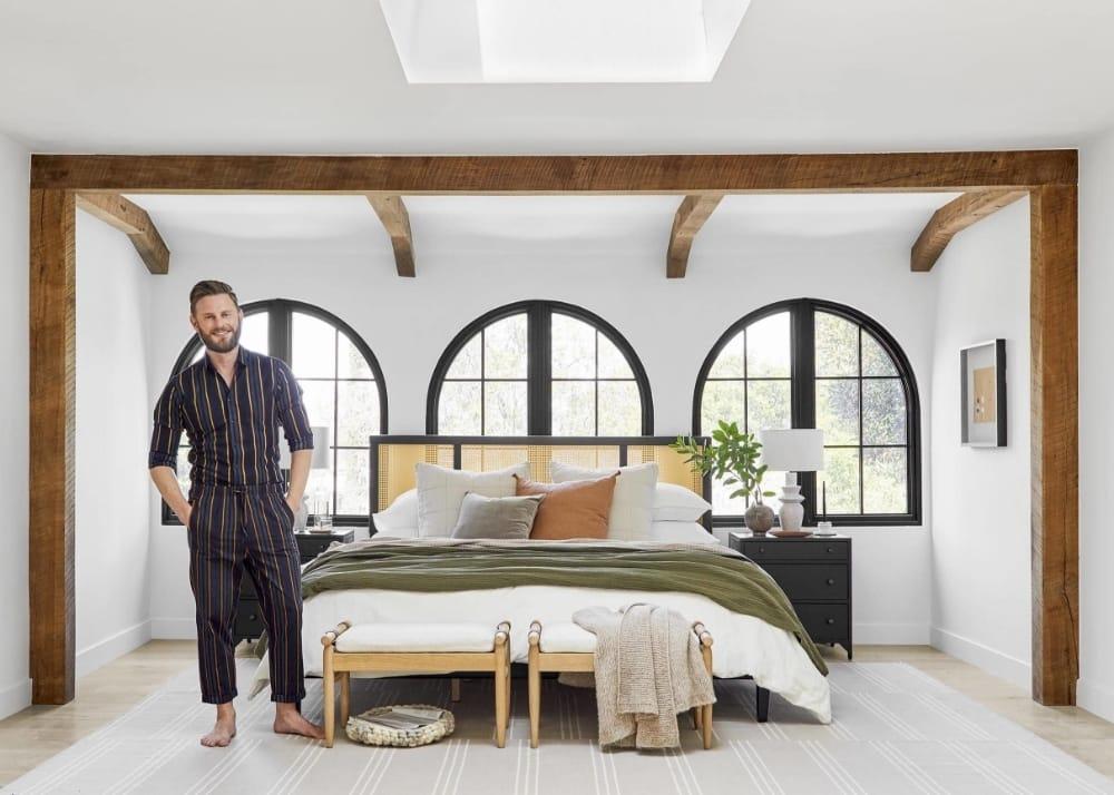 Interior designer Bobby Berk standing under a skylight in a bedroom