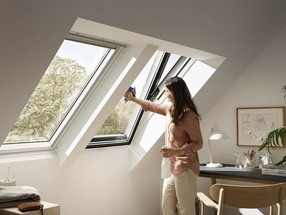 A woman cleaning a skylight.