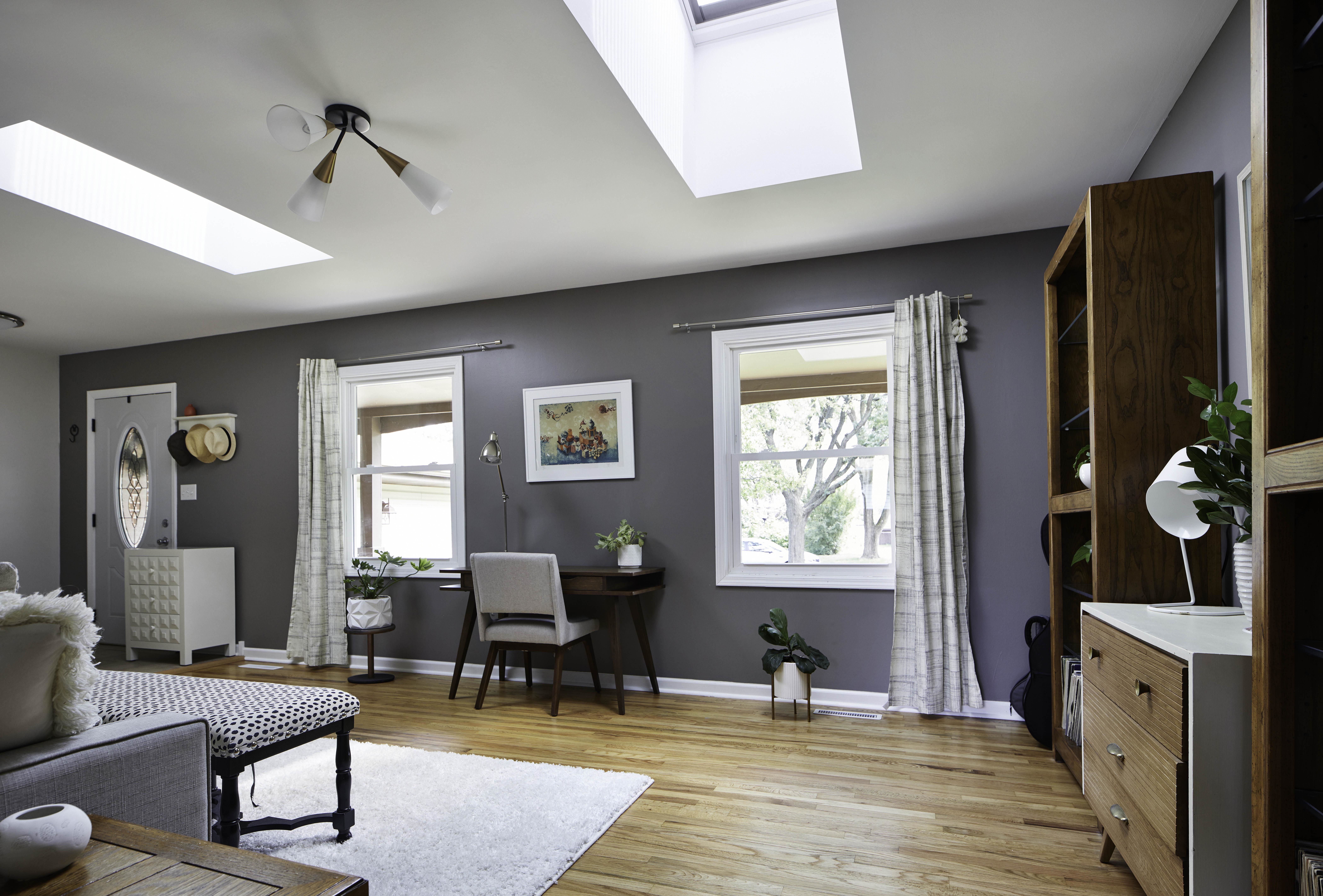 living room with two skylights and a home workspace
