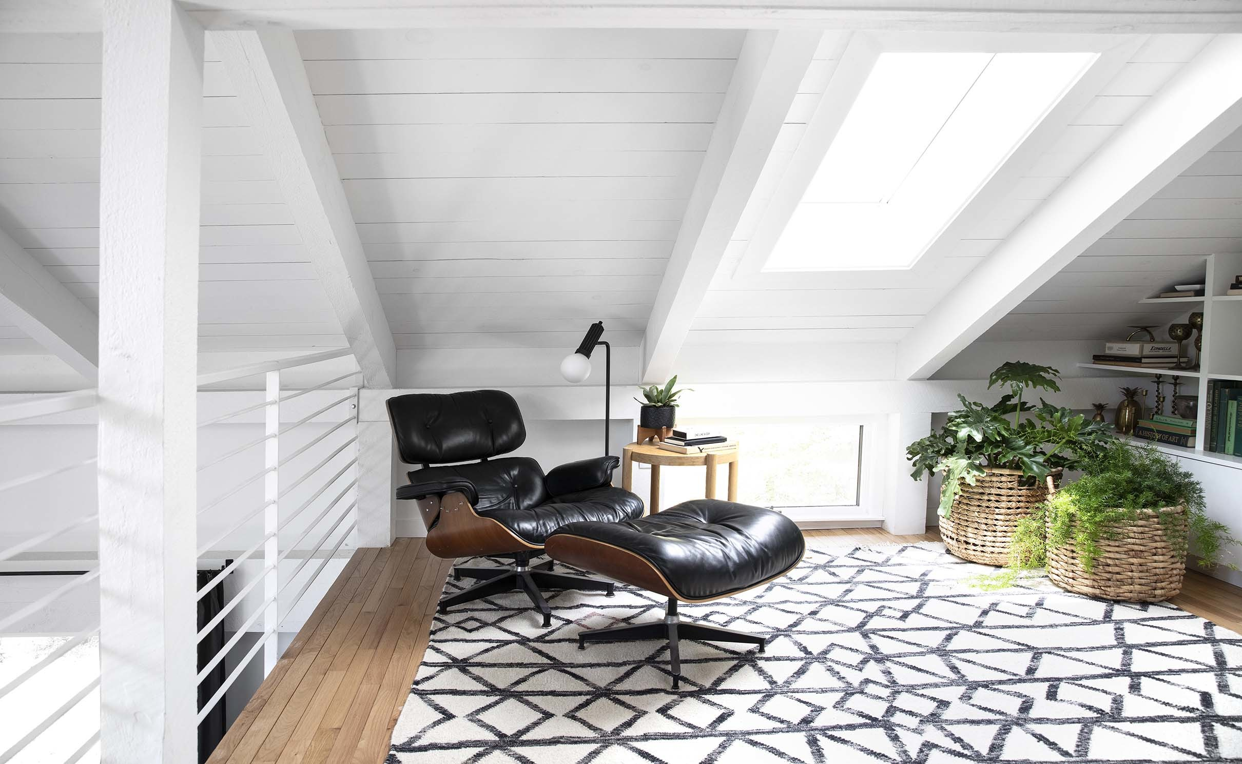 Black Eames chair under a skylight in a white wood clad room with built-in bookshelves and a geometric print rug