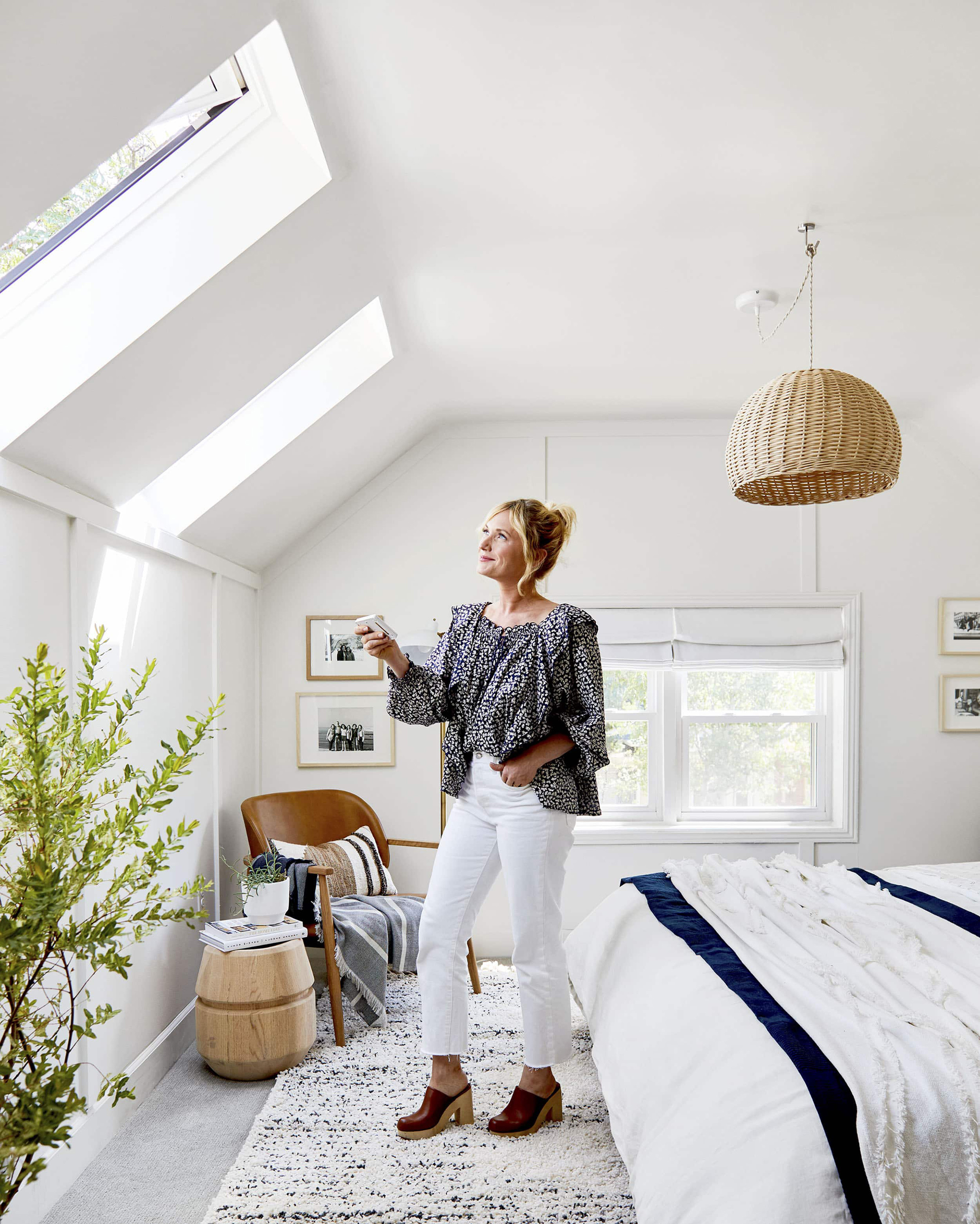 A woman stands in a bedroom under two skylights