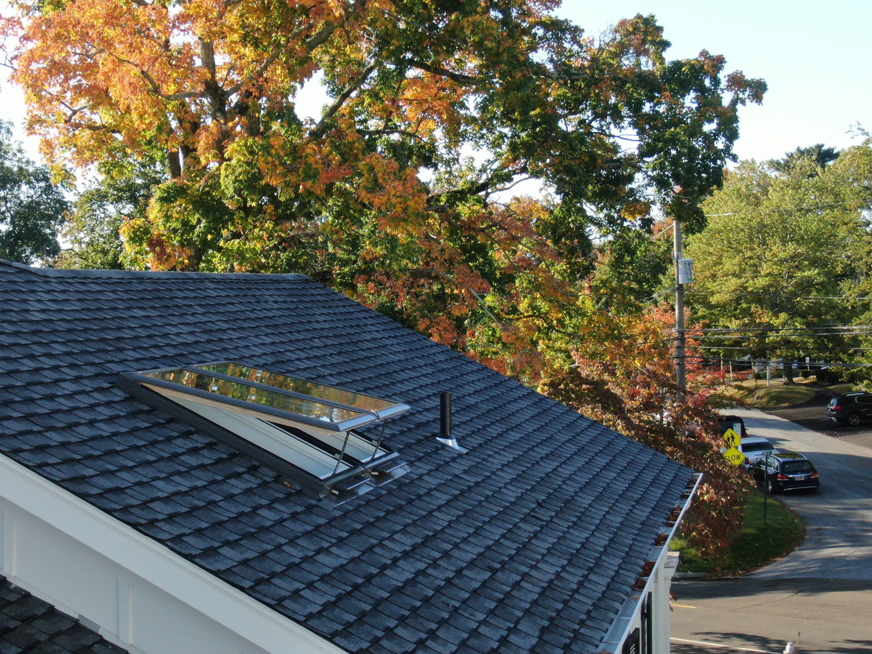 Roof view of an open skylight on a fall day