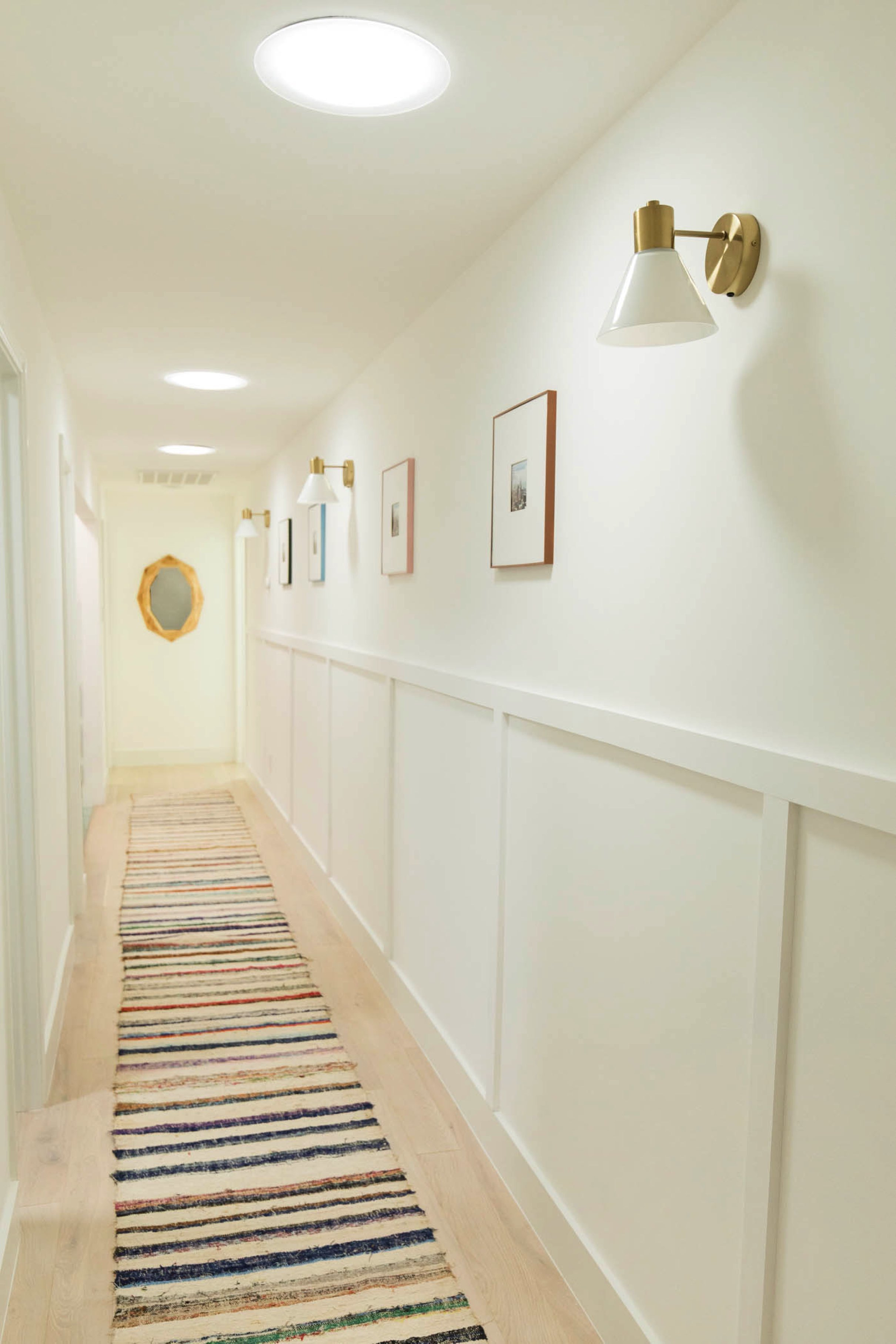 Hallway with three sun tunnel skylights, a striped runner rug and decorative wall panels