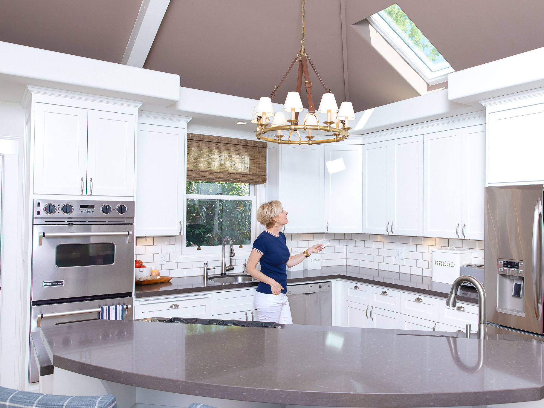 woman in a kitchen using a remote control to open the skylight above