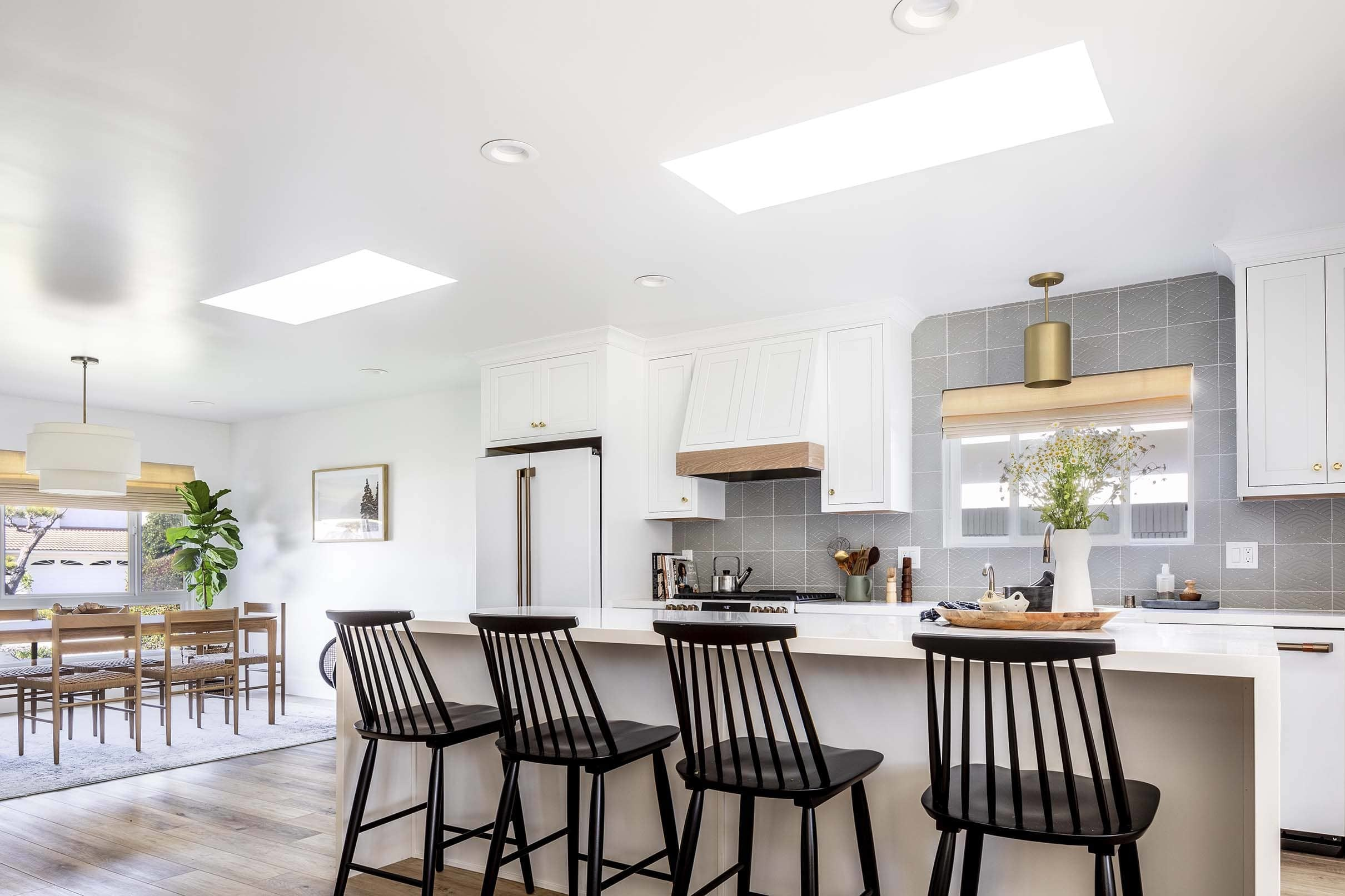 Two skylights brighten an all-white kitchen that includes white appliances, a grey backsplash, white waterfall island and black Shaker-style counter chairs