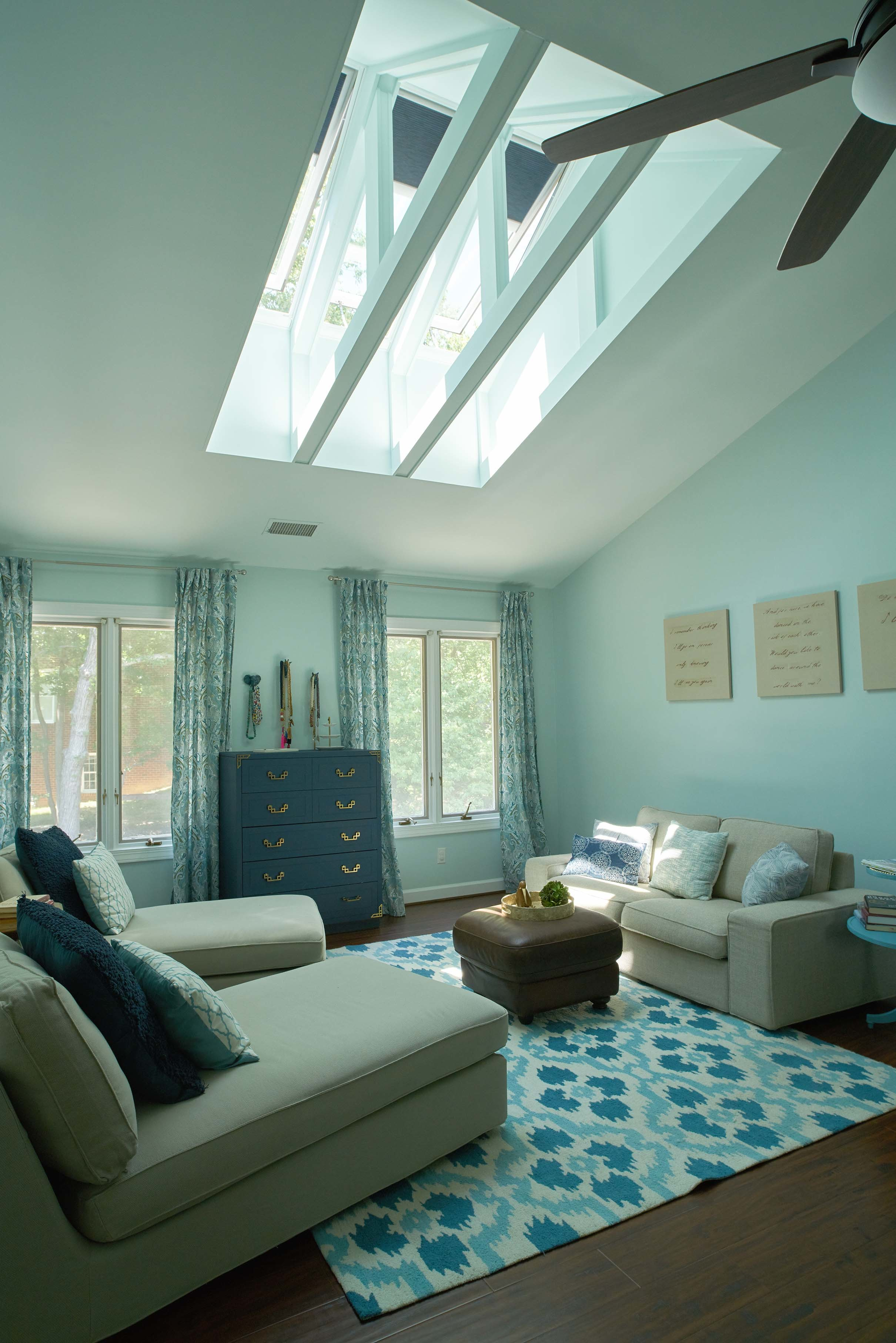 three skylights installed in between exposed roof trusses over a blue and green living room
