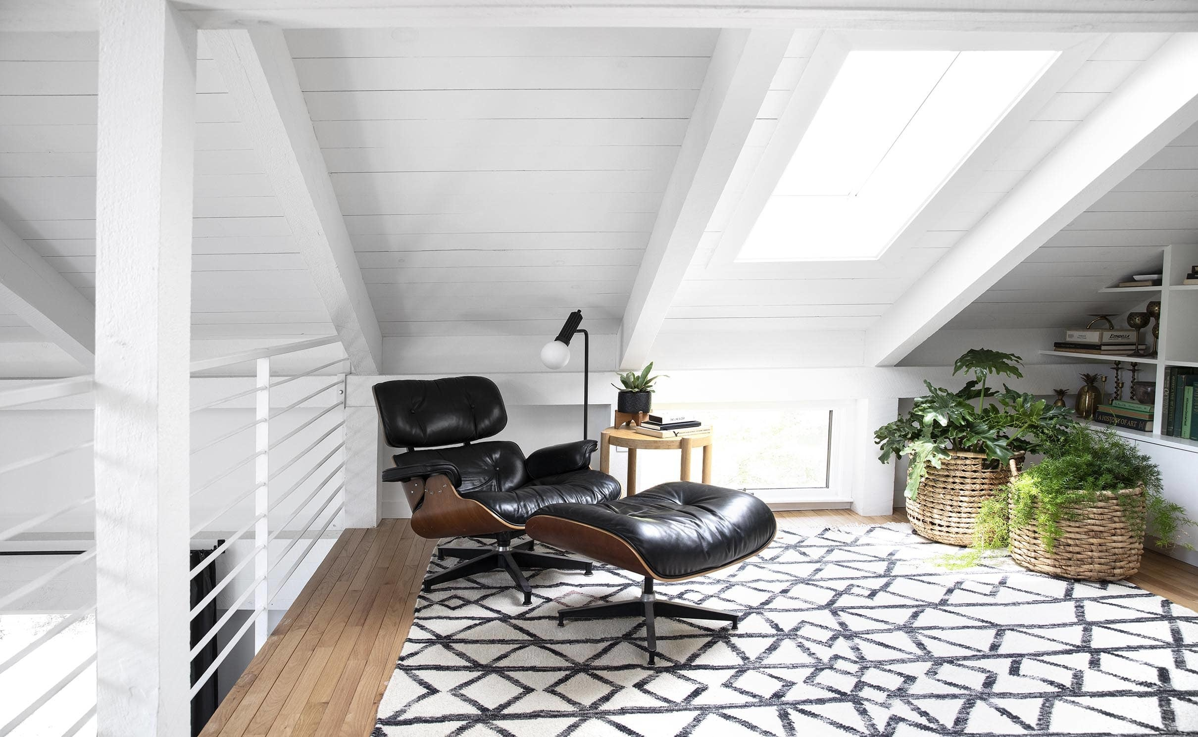 loft with skylight and black lounge chair white painted wood ceiling