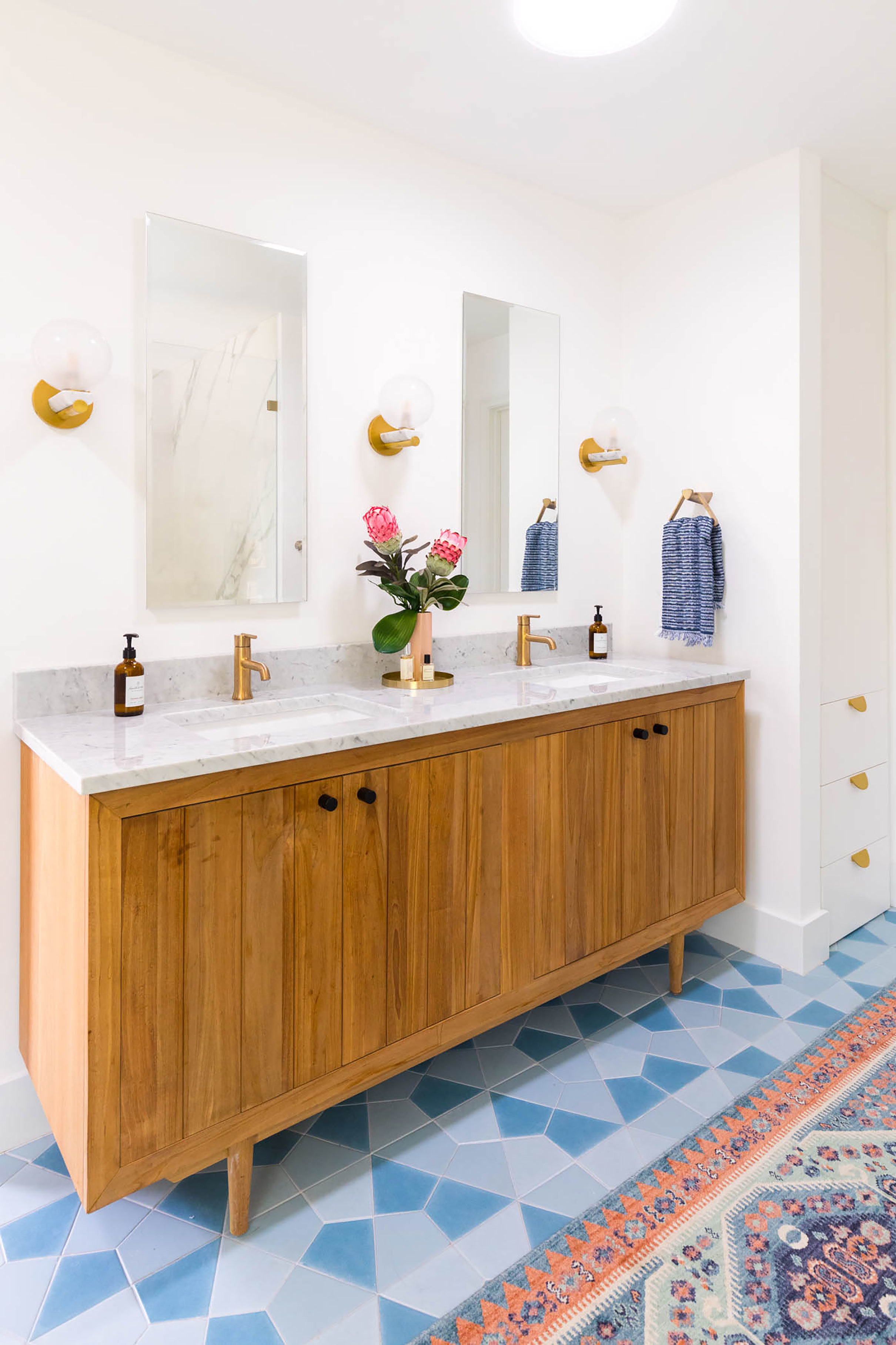 A blue and white bathroom with pink accents and Sun Tunnel skylights