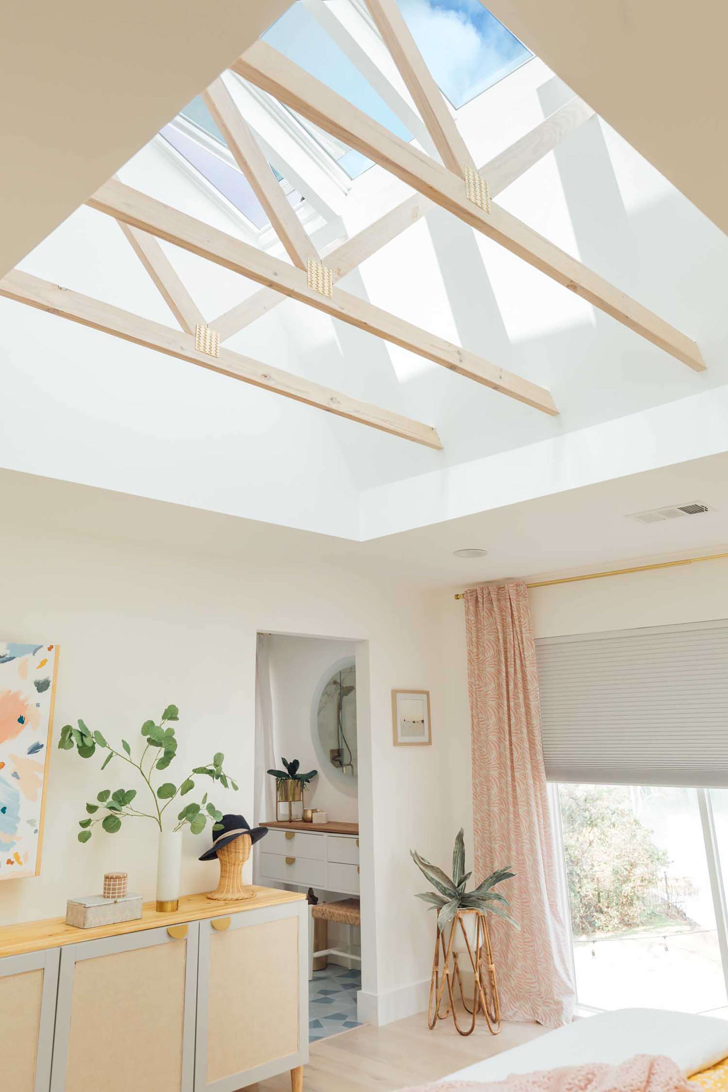 Bedroom with pink and yellow color accents and three skylights with exposed trusses.