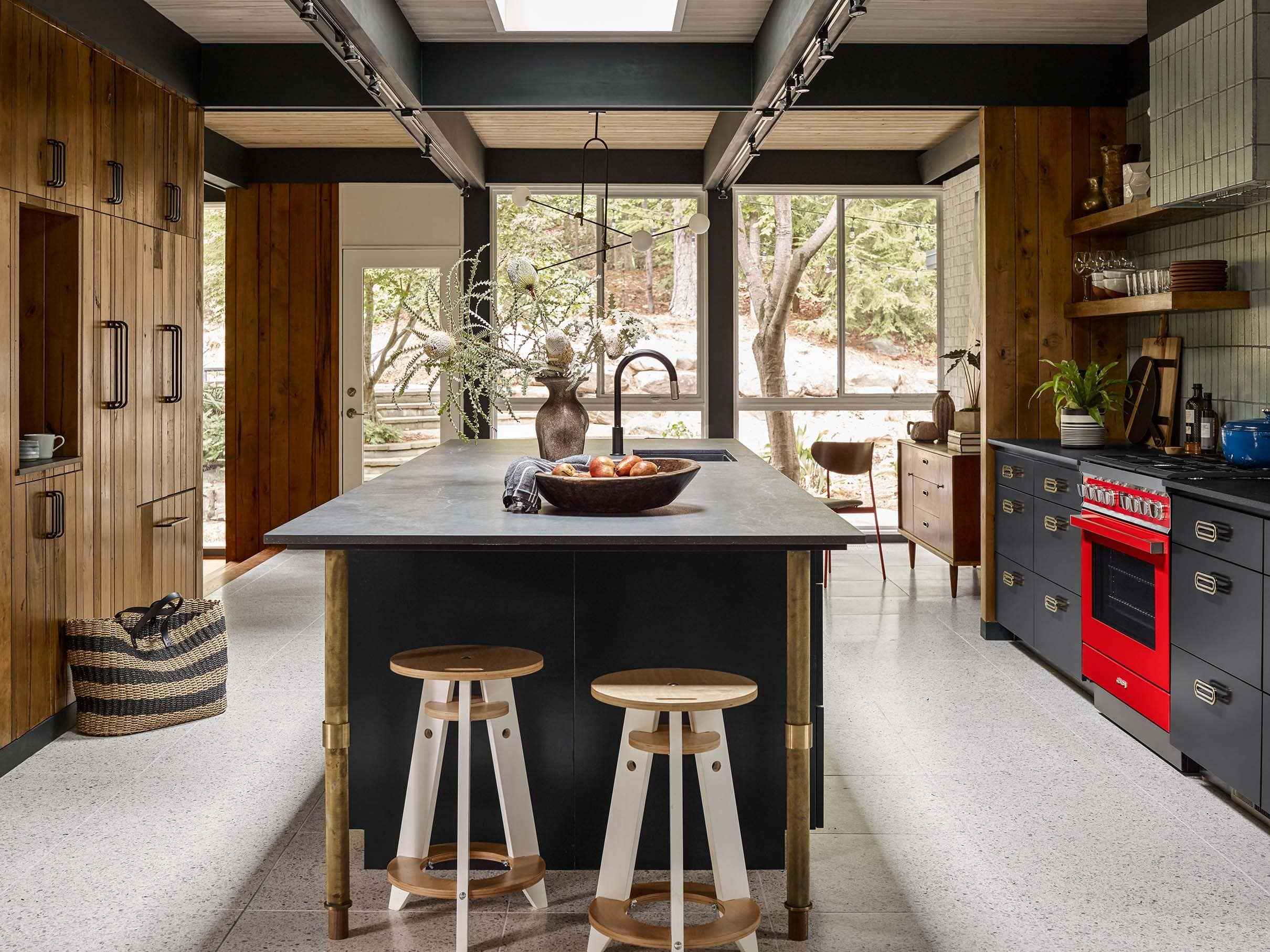 Modern kitchen with skylight over island red oven natural wood cabinets