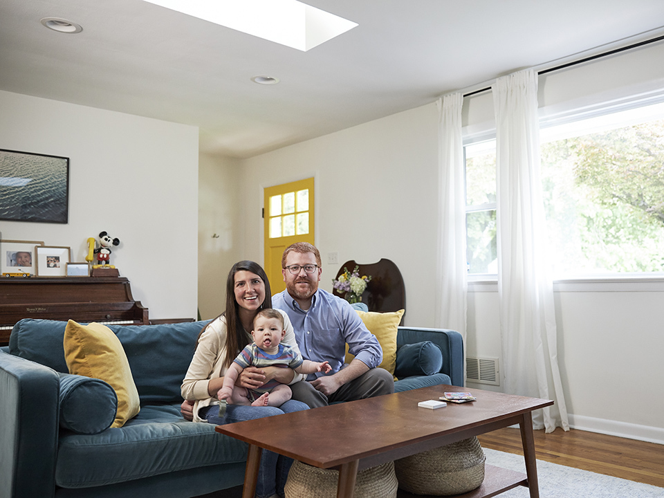 mom dad and infant sitting on a blue couch under a skylight in a living room