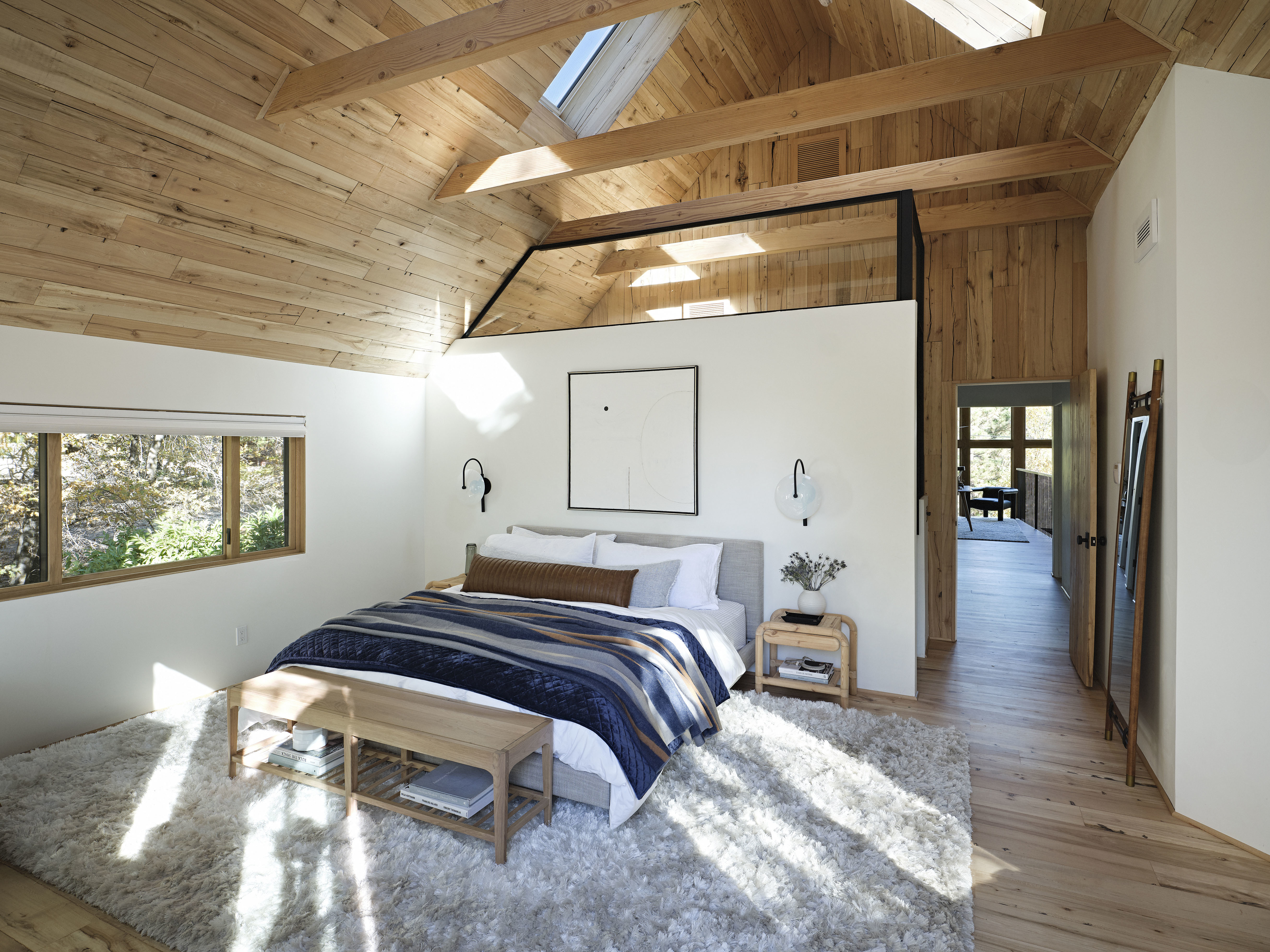 Bedroom with wood clad ceiling, four skylights and a bed layered with blue and terra cotta blankets