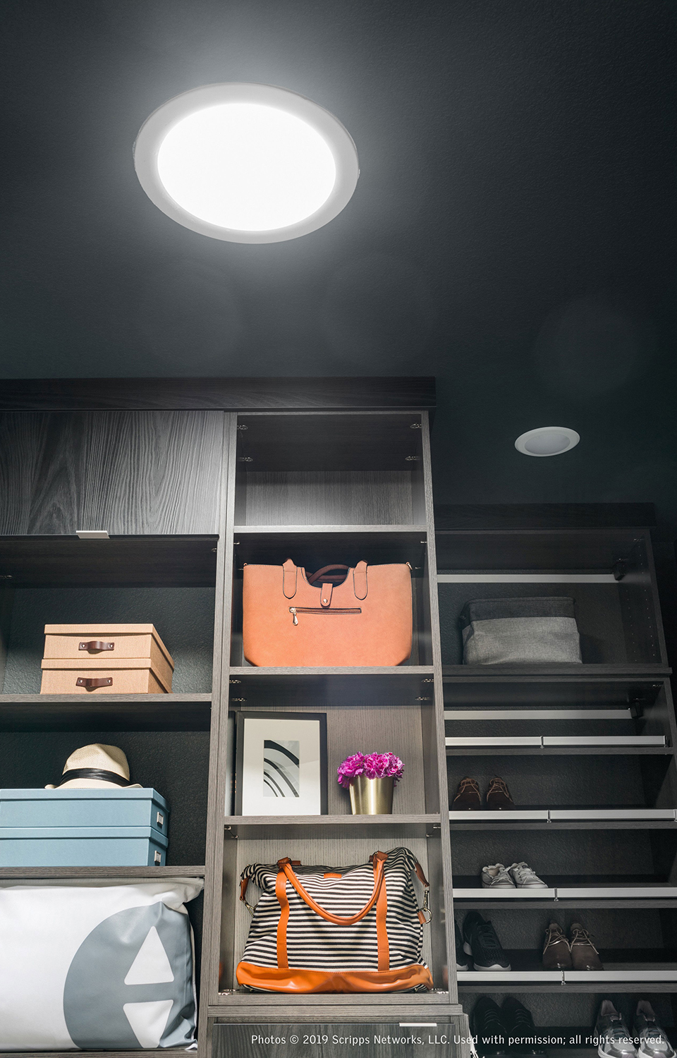 Walk in closet with dark grey walls and natural light from a Sun Tunnel skylight