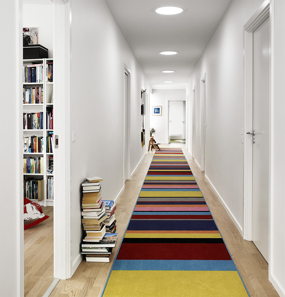 Hallway with colorful striped rug and three Sun Tunnel skylights