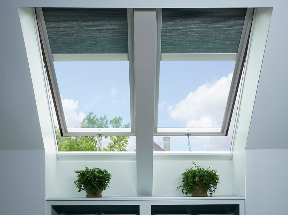Two skylights with gray blinds over a built-in shelf