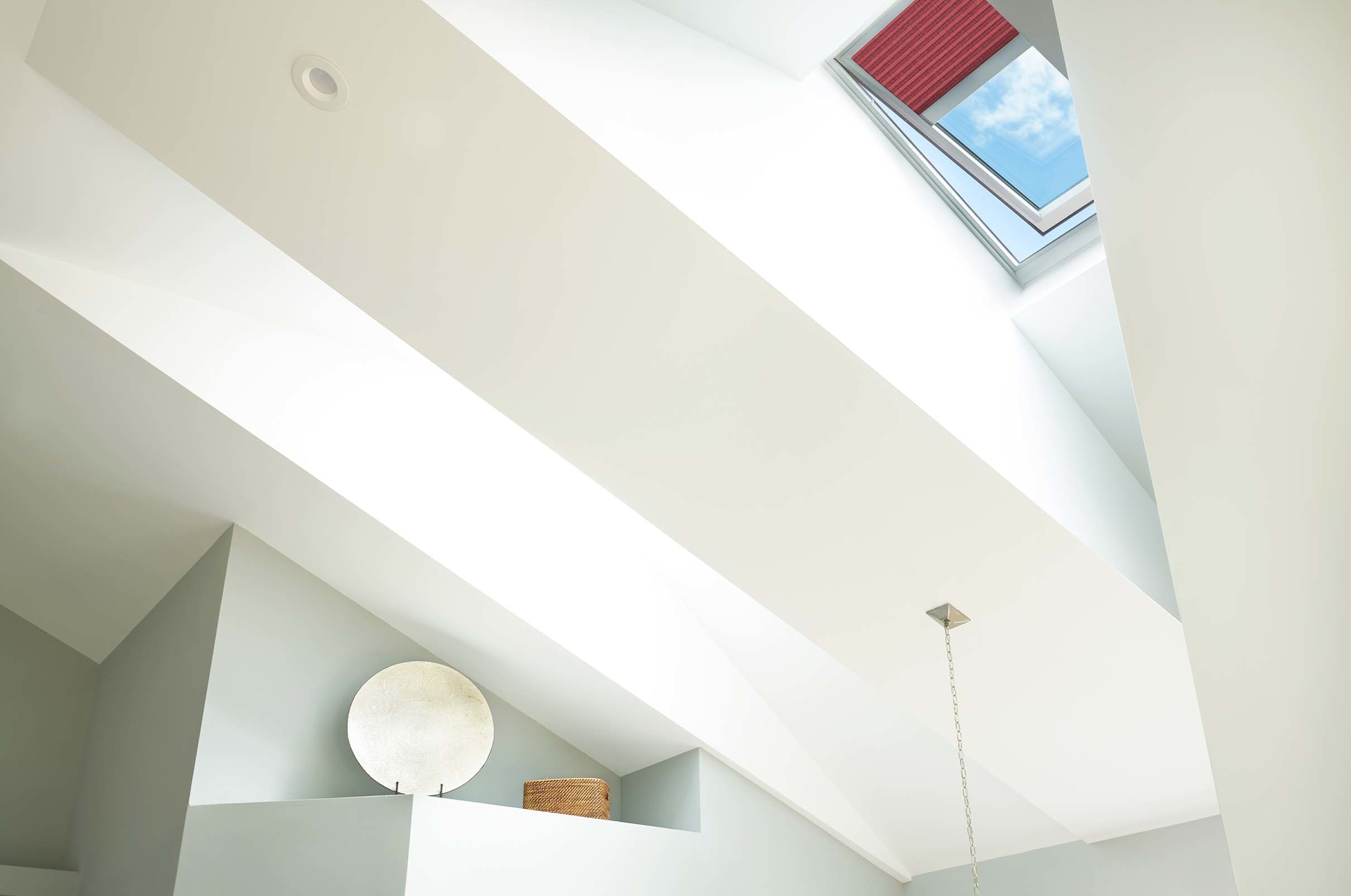Skylight in a vaulted ceiling with a red shade partially extended