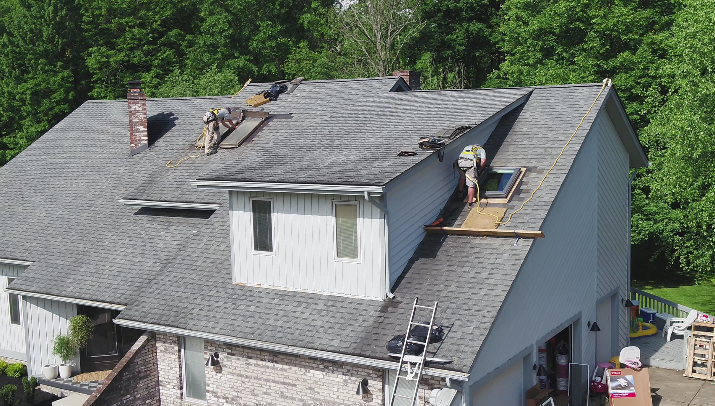Two workers install skylights on a roof