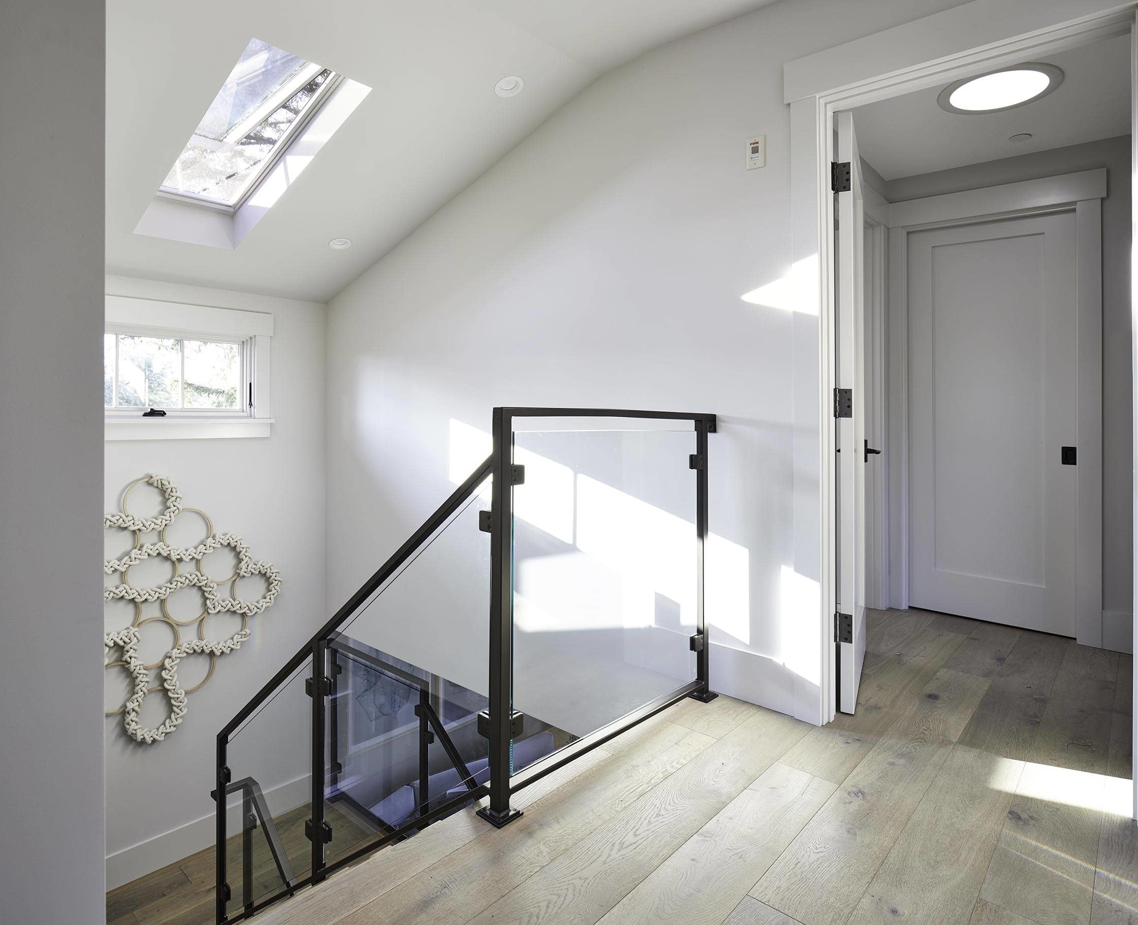 Sunlit stairwell with a skylight and knot art