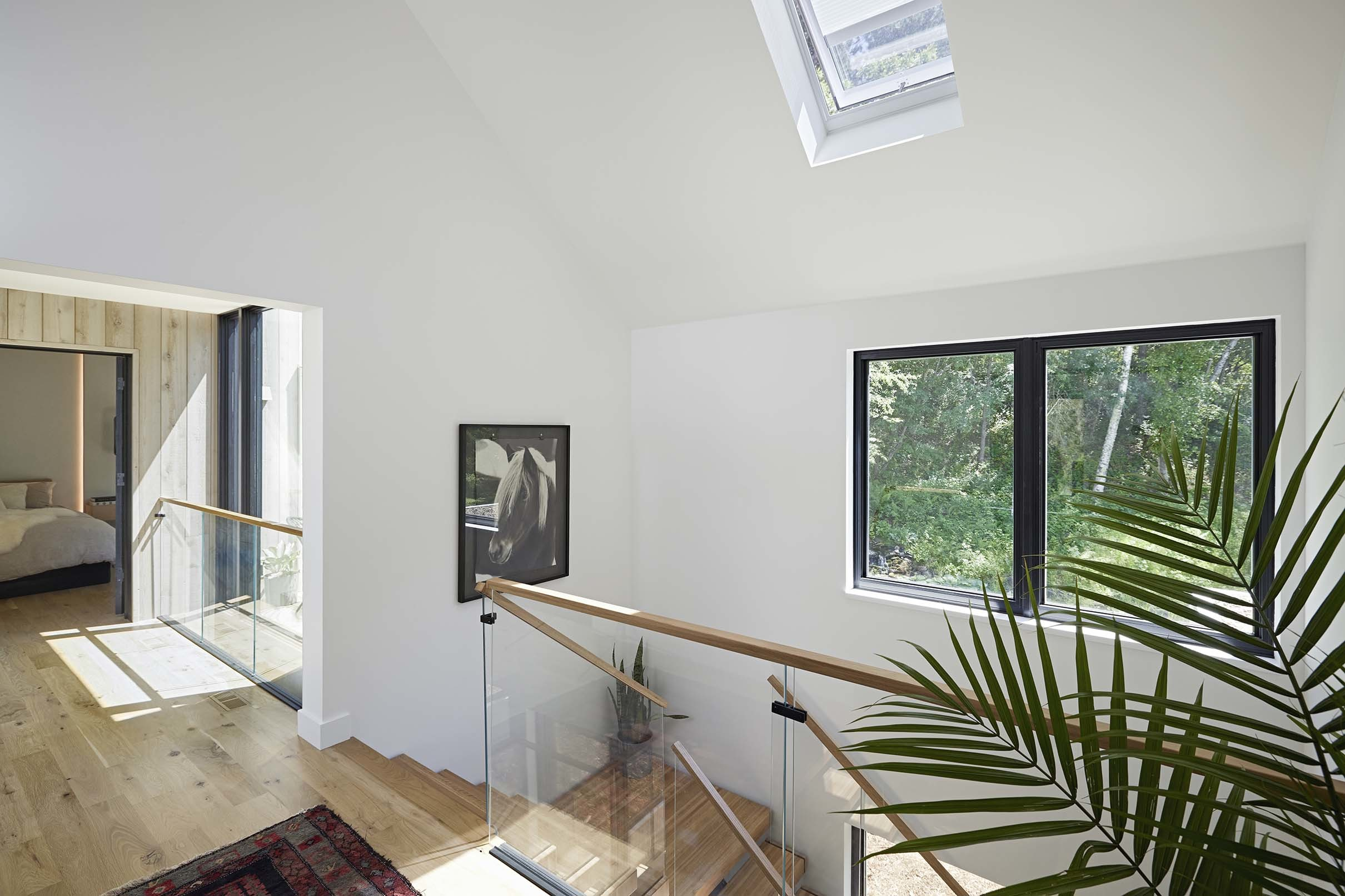 a stairwell brightened by a skylight white walls and blond wood floor