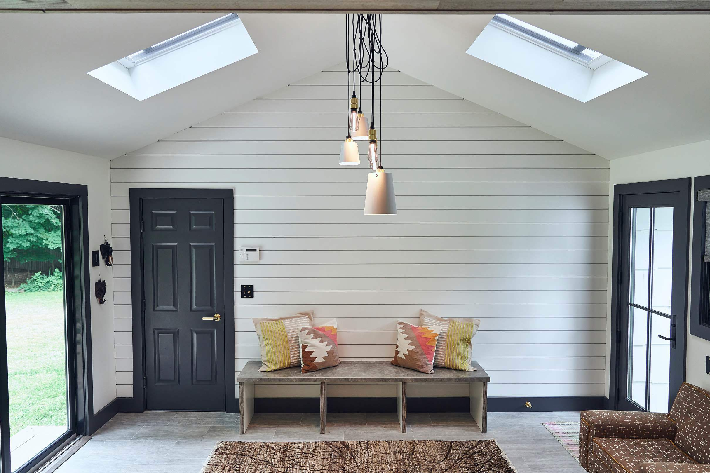 A sunroom with two skylights on either side of the roof ridge, a shiplap wall with a bench centered on it and pillows