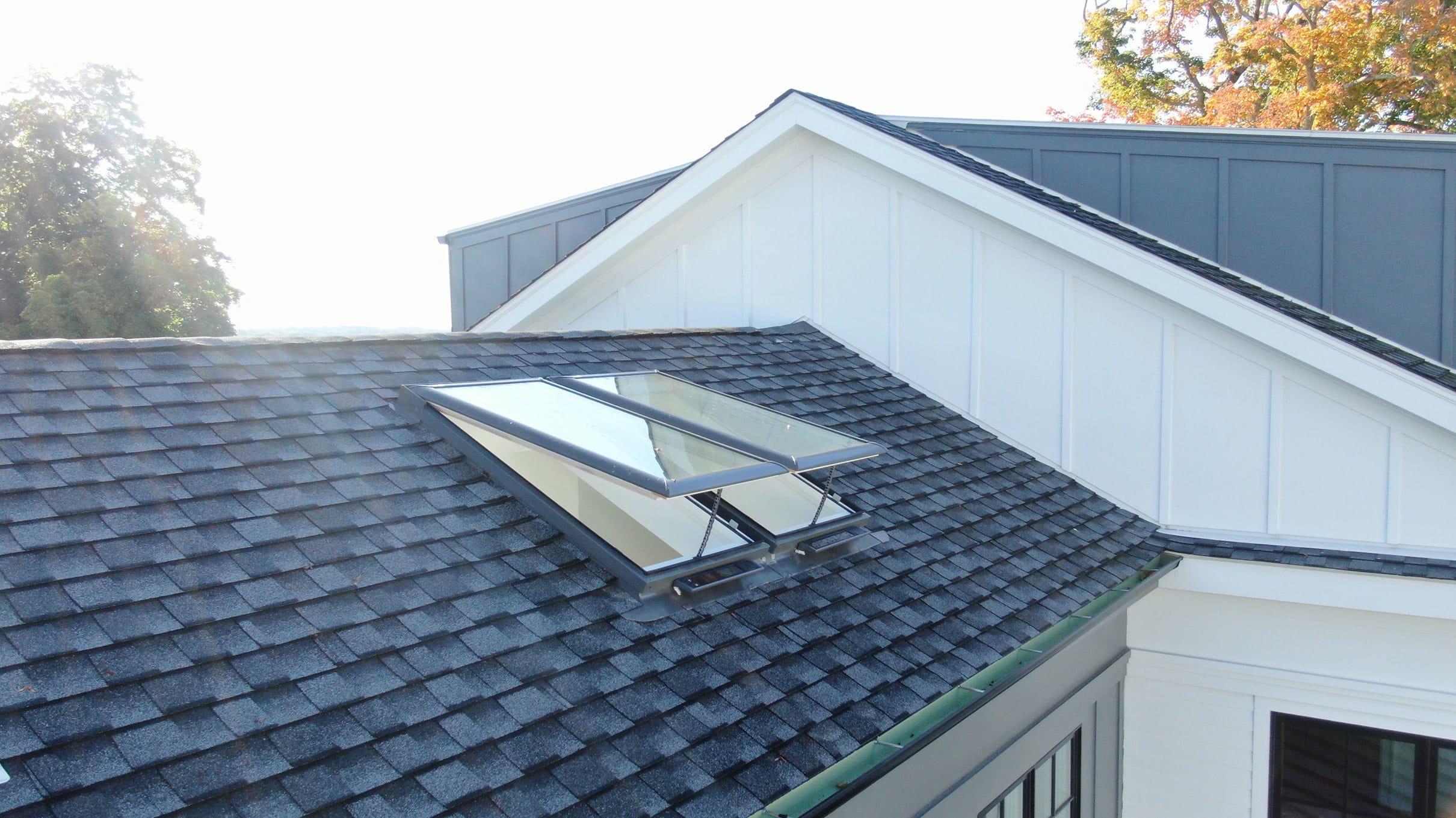 Two open skylights on a shingle roof
