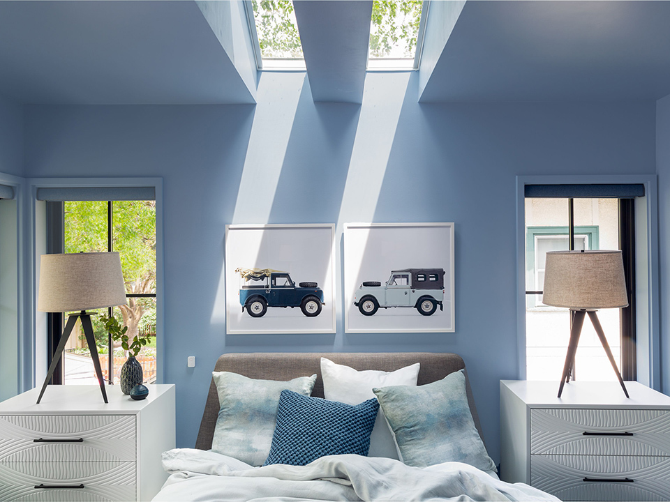 master bedroom with sky blue walls and two skylights