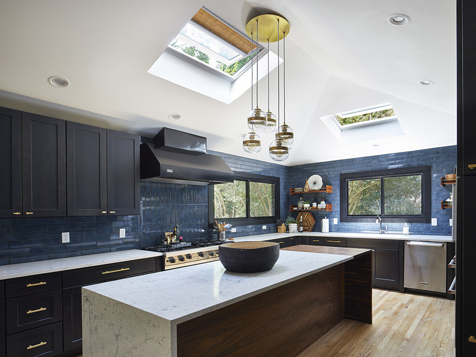 kitchen with black cabinets blue backsplash and two skylights