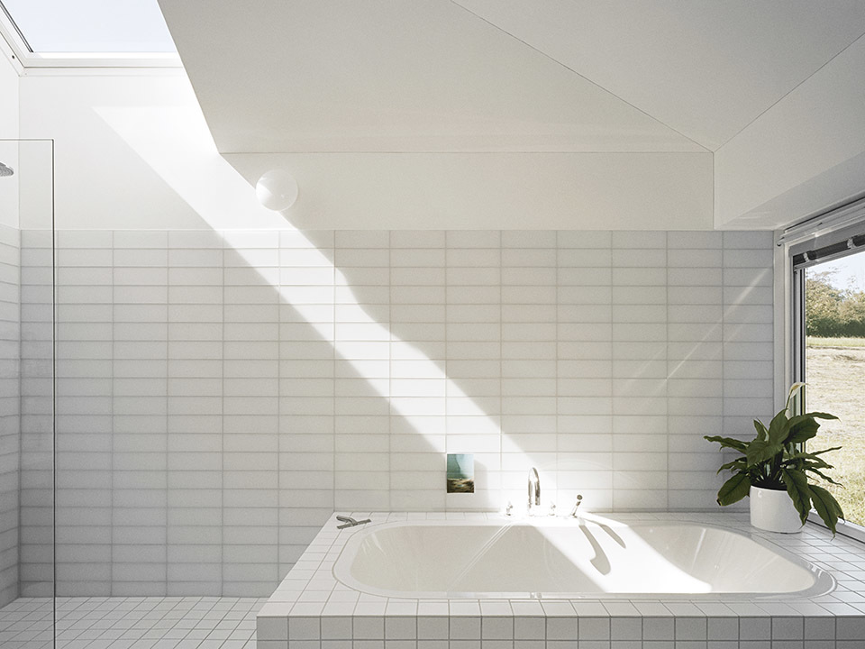 White tile bathroom with a skylight that has sun shining through it.