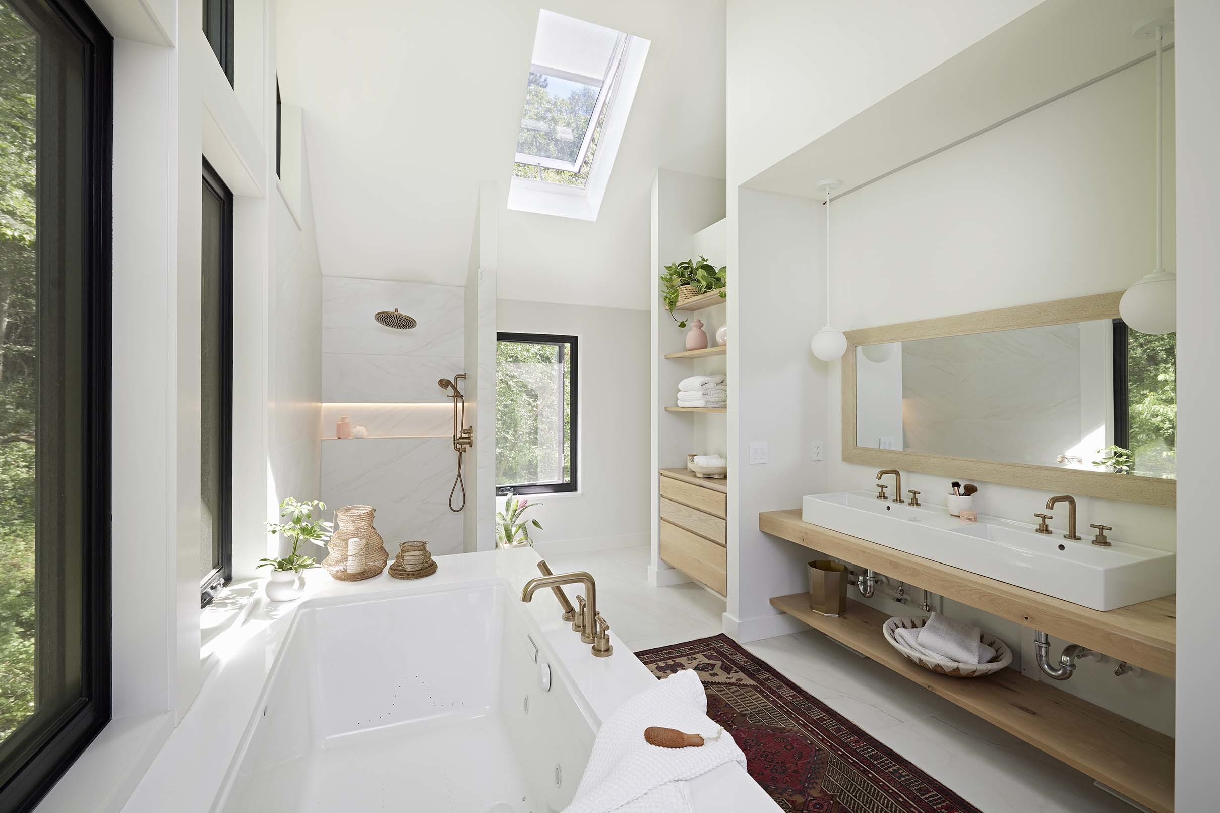 Galley style bathroom with a skylight over the shower and a long vanity