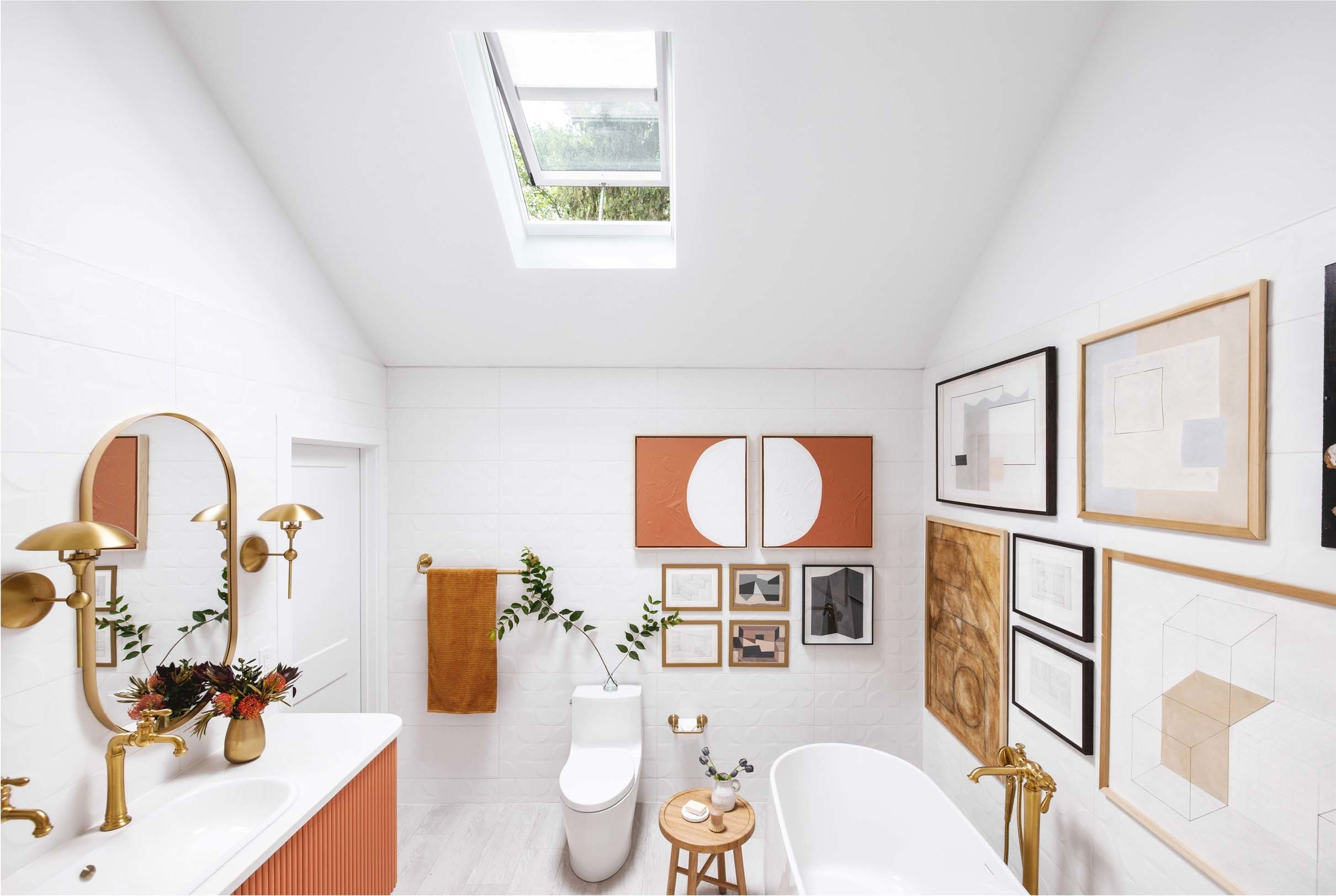 white and terracotta bathroom with skylight over a gallery wall flanking a bathtub