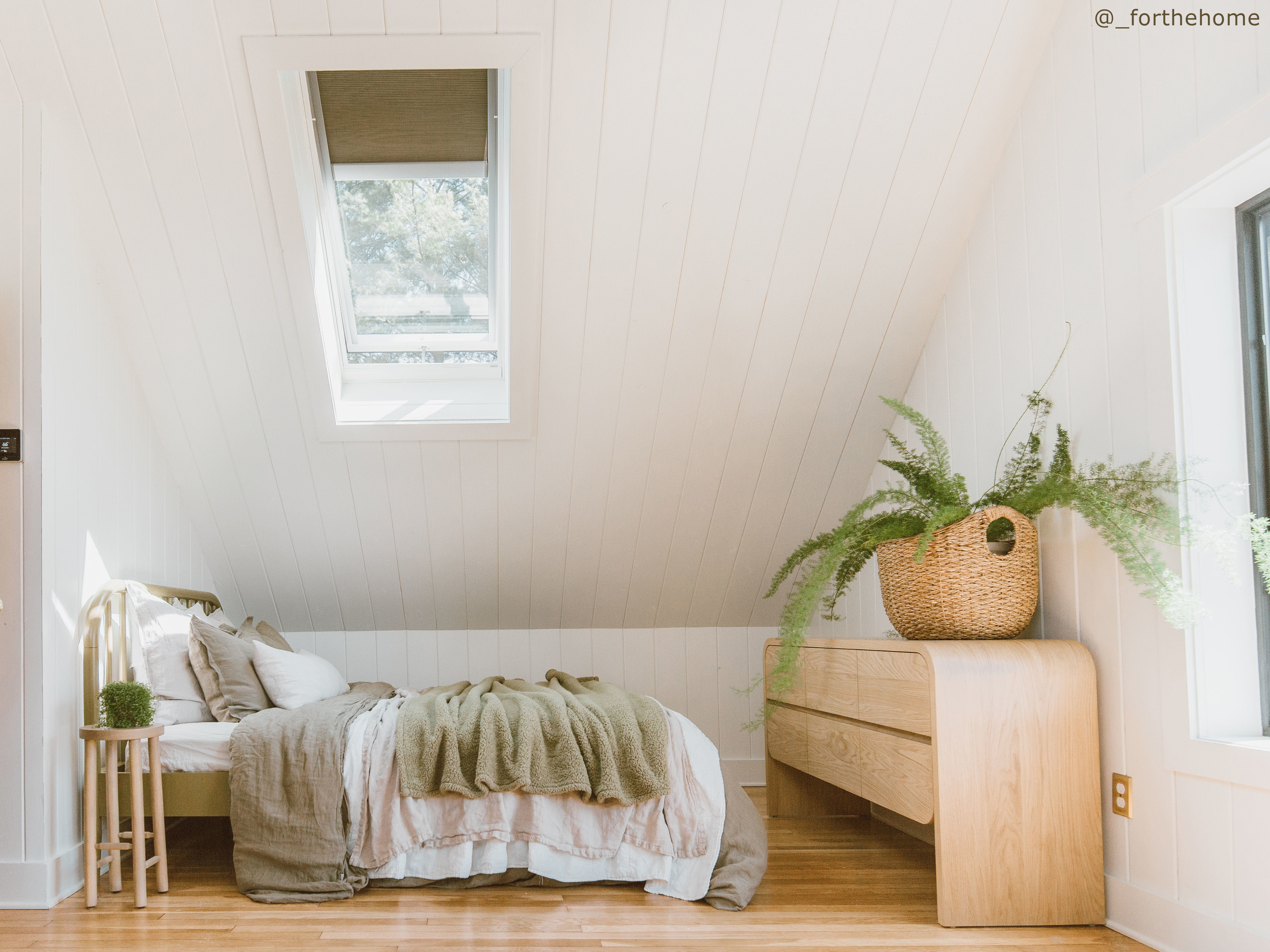 Bedroom with blond wood floors white shiplap walls and a skylight with room darkening blinds.