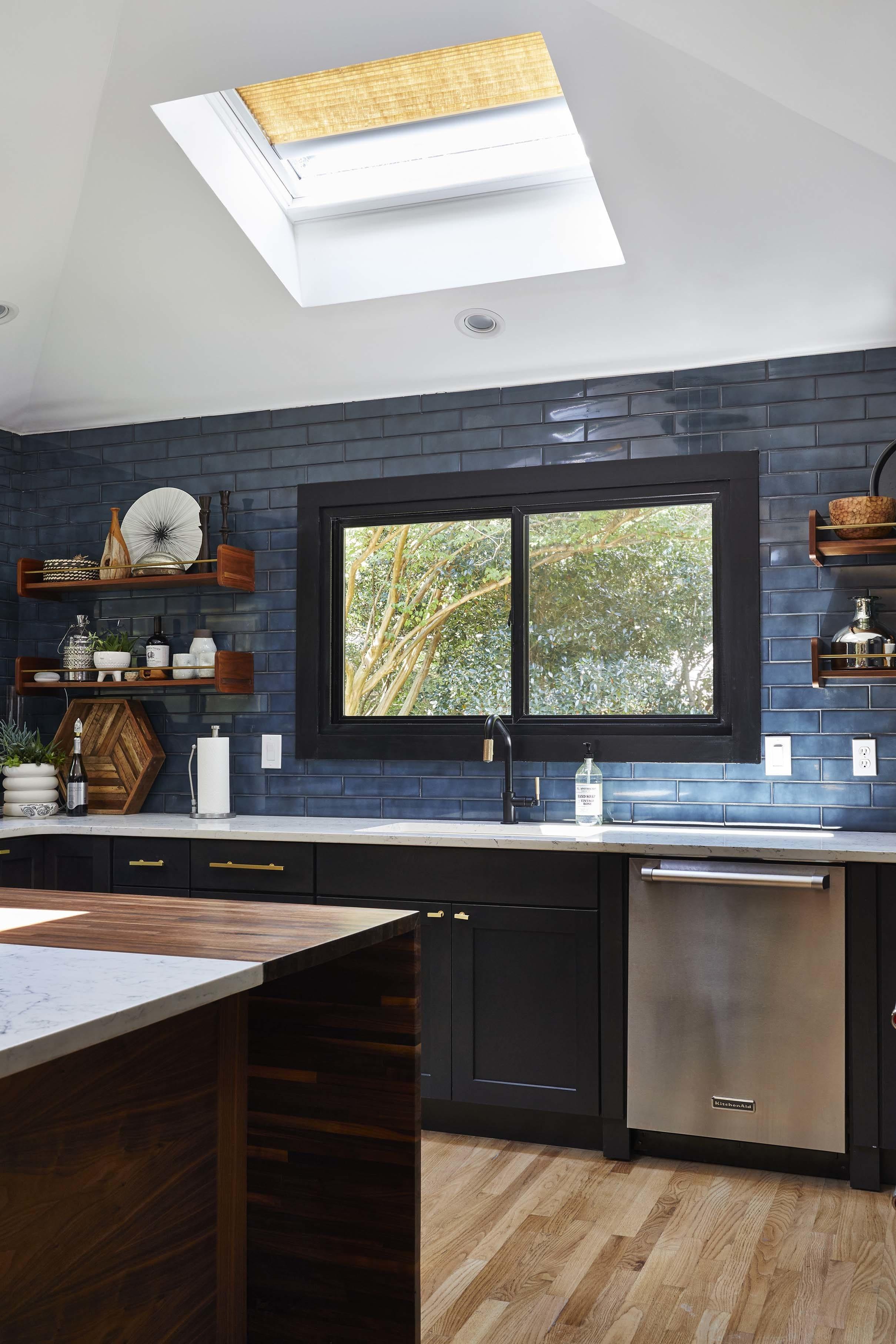 Kitchen black cabinets blue backsplash skylights
