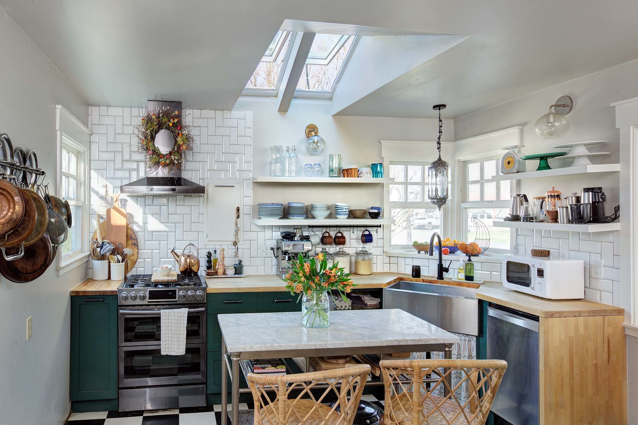 A white and green kitchen with two skylights