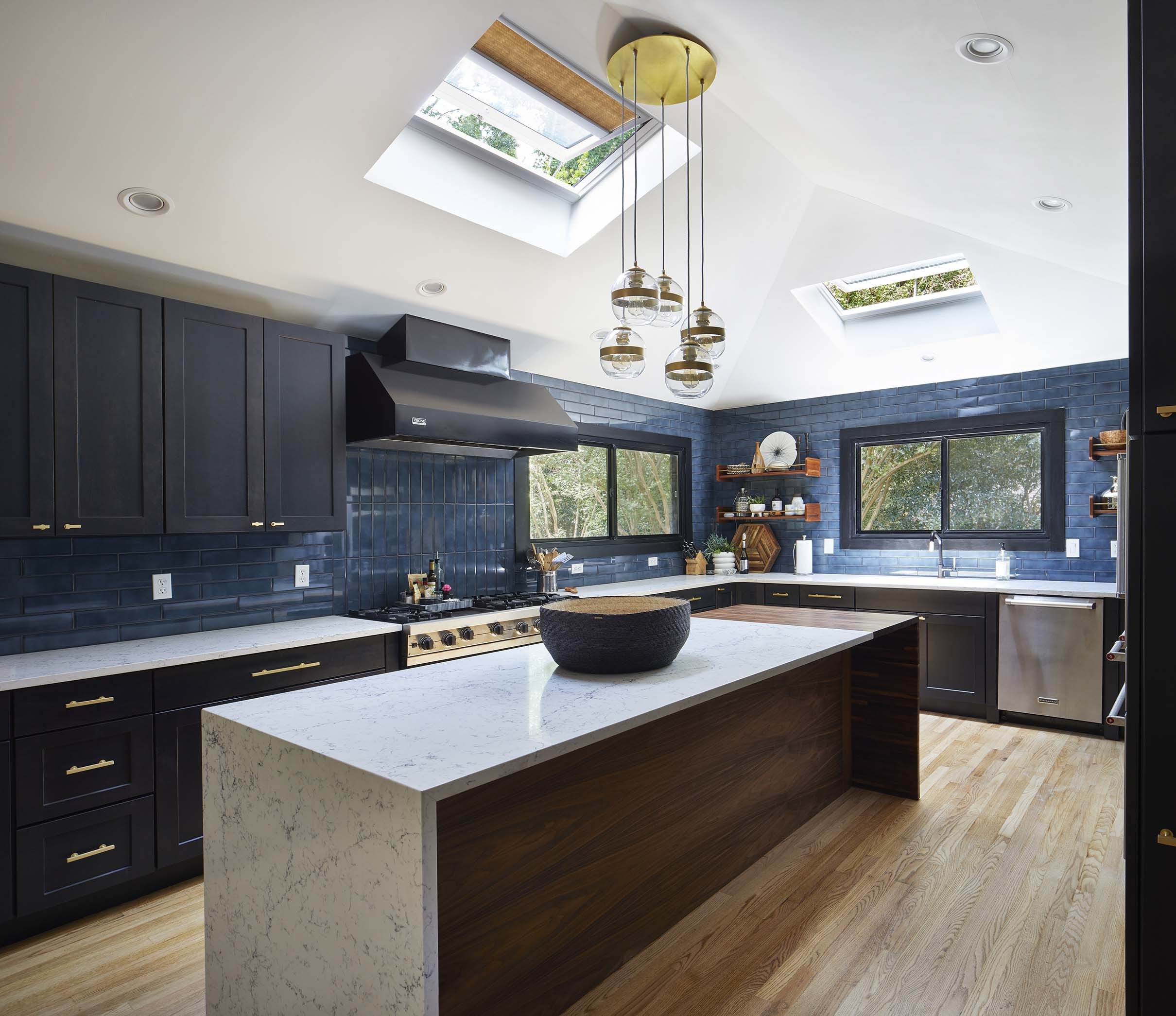 Kitchen two skylights with gold shades black cabinets brass hardware