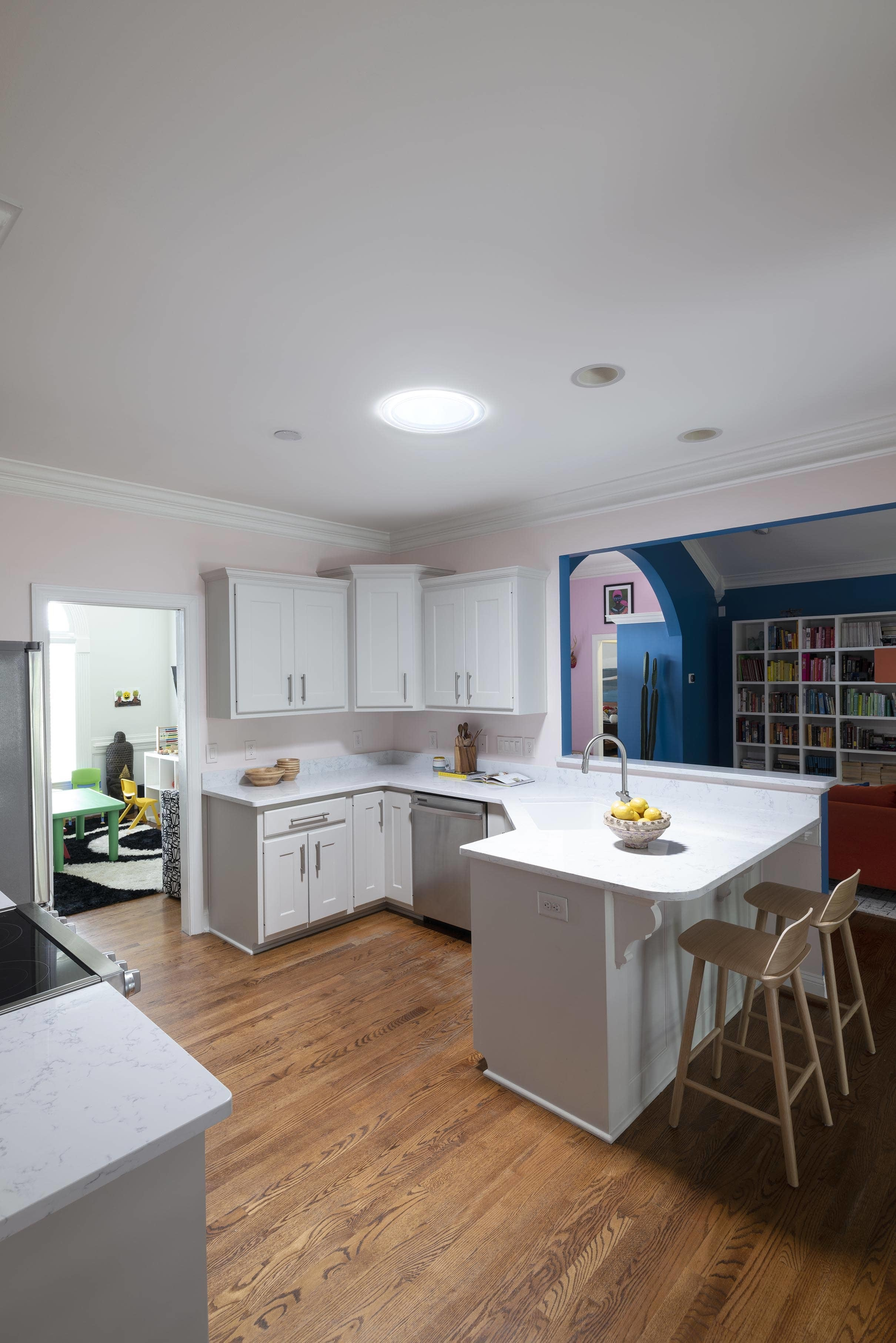 kitchen with light pink walls, white cabinets and a Sun Tunnel skylight with a blue living room in the background