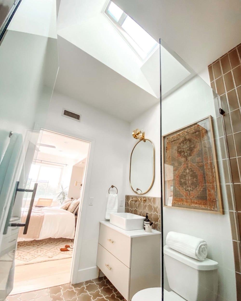 small bathroom with a skylight tan tile and a bras frame mirror
