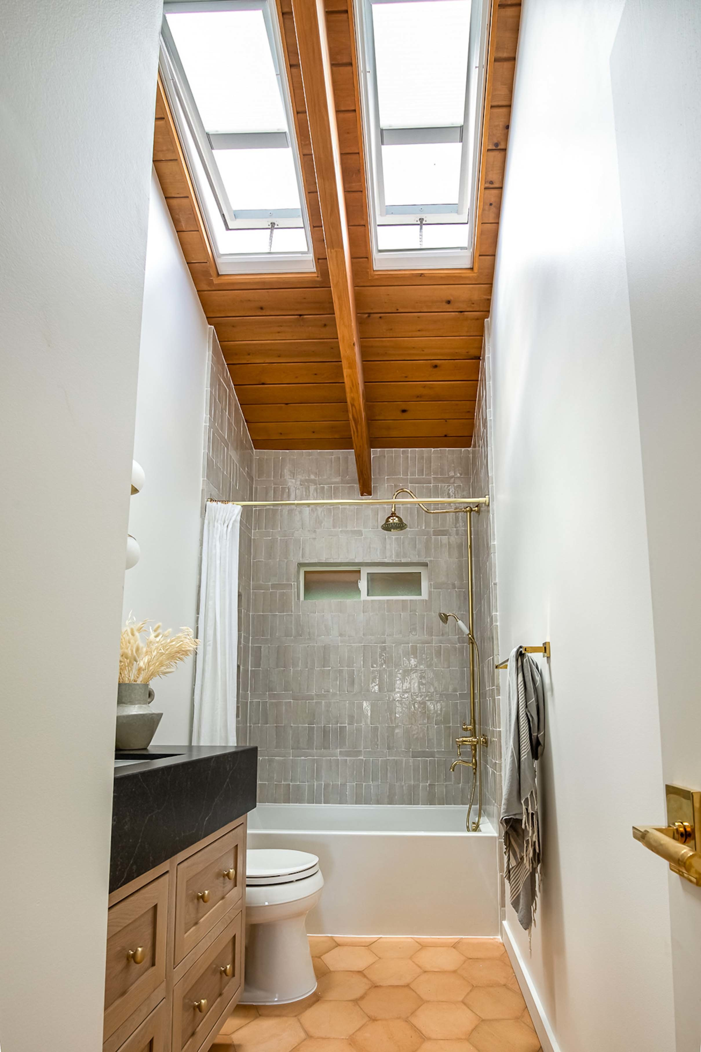Small bathroom with two skylights in a wooden ceiling