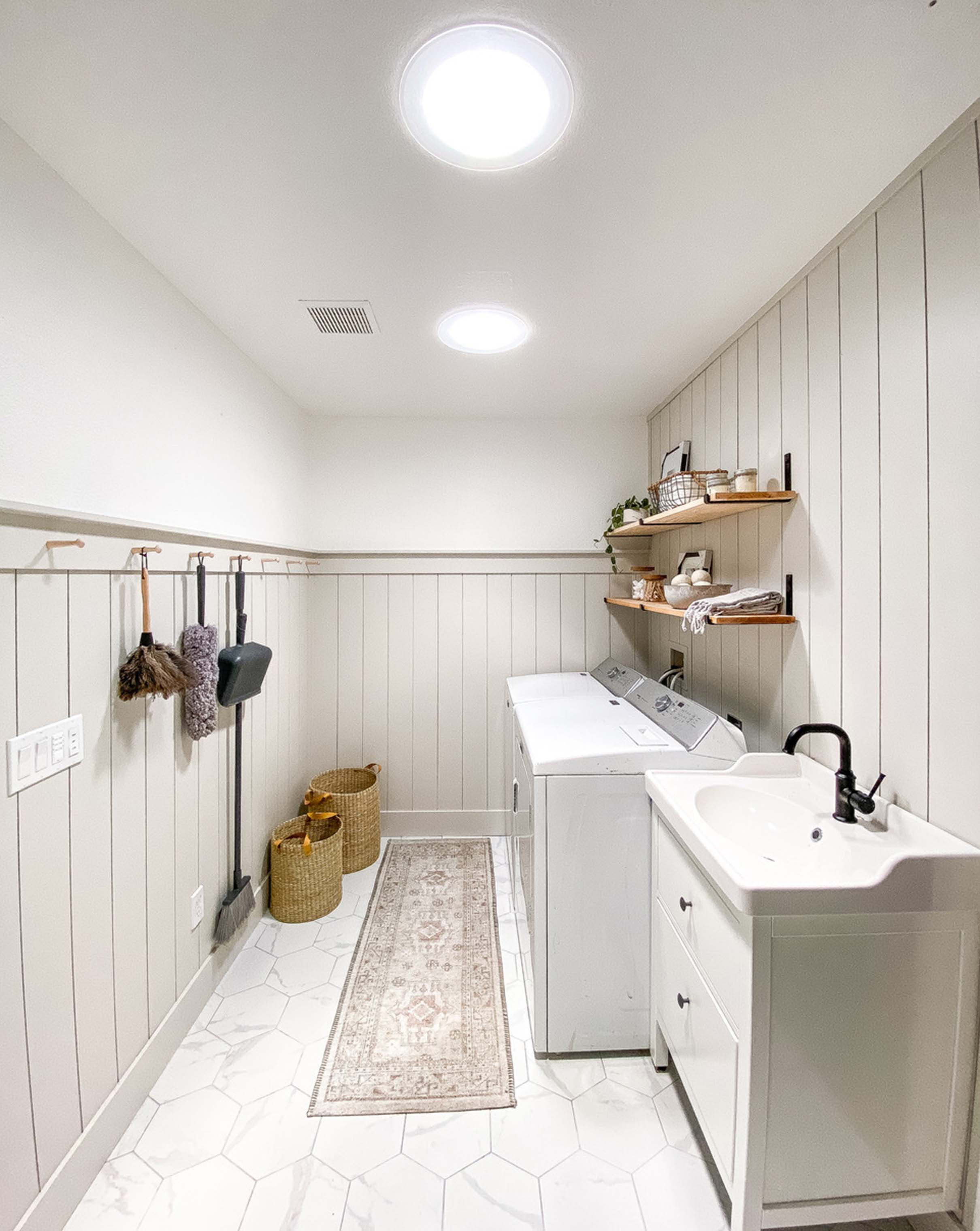 two sun tunnels brighten a white and greige laundry room