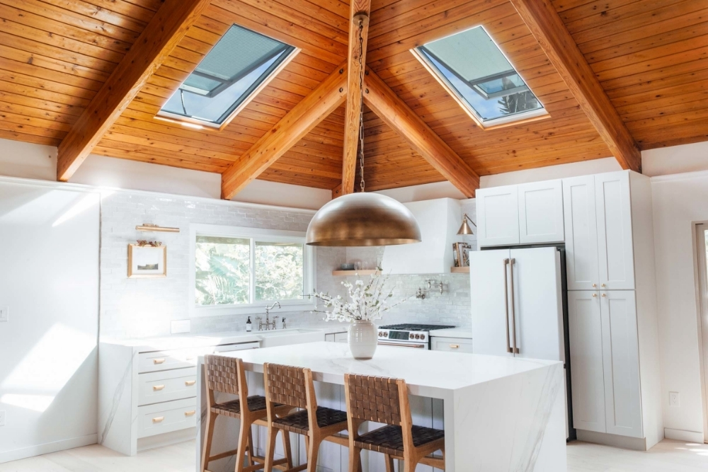 White kitchen with natural wood ceiling two skylights and brass light fixtures